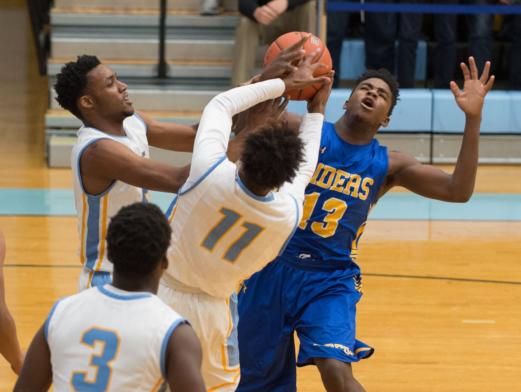 Cape Henlopen's Randy Rickards (5), left, and teammate Sh'Kai Chandler (11) battle for a loose ball against Caesar Rodney's Kairi Buie (13) during their game at Cape Henlopen High School.