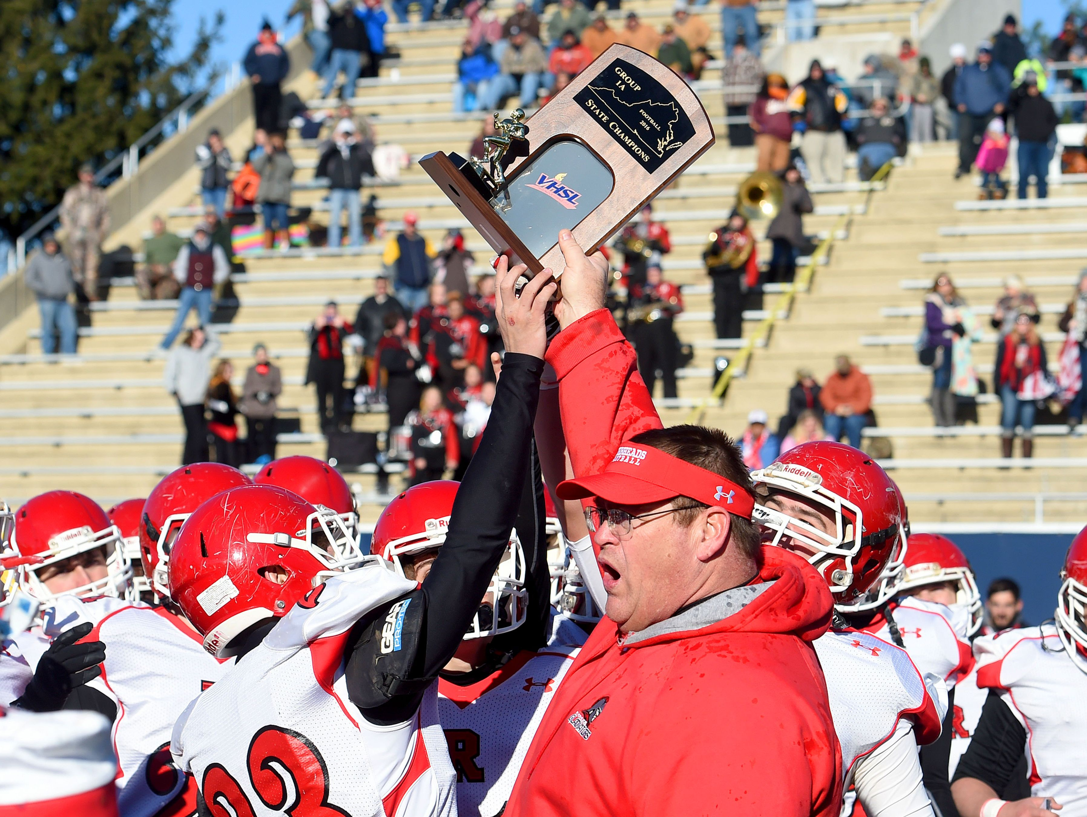 Riverheads' head coach Robert Casto holds high the Group 1A state championship trophy as he gives it to his players after defeating Sussex Central in a game played in Salem, 49-6.