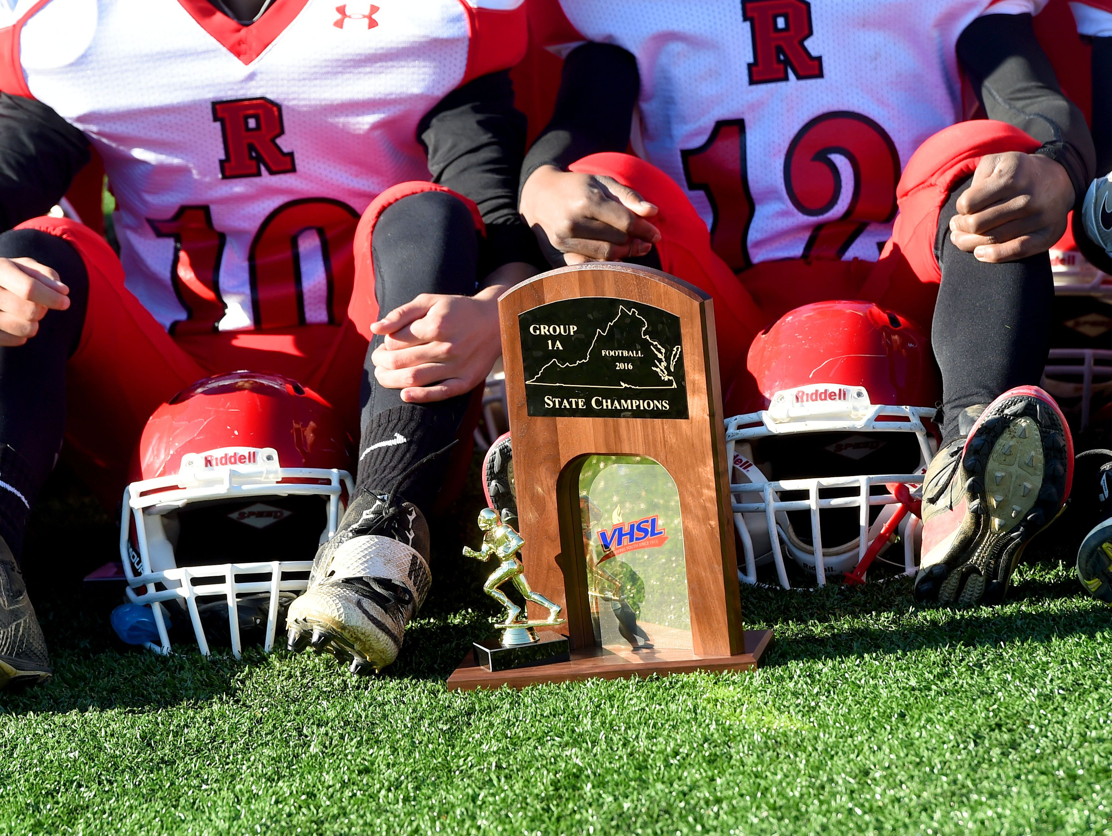 The Group 1A state championship trophy is on the ground at the feet of the Riverheads' football team as they gather for a group photo after they defeated Sussex Central to win the state championship, 49-6.