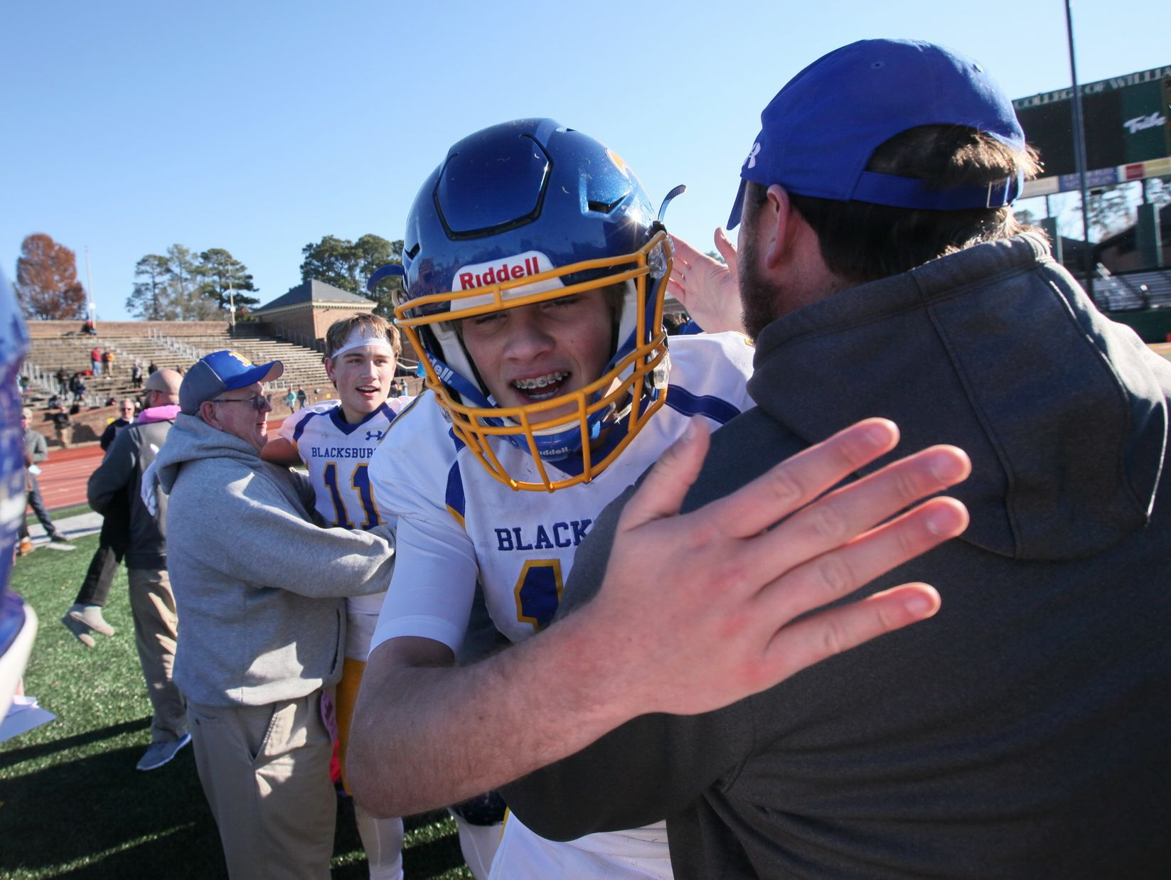 Blacksburg quarterback Grant Johnston gets a hug from his dad, assistant coach Chad Johnston, after winning the 3A state championship over Staunton River.