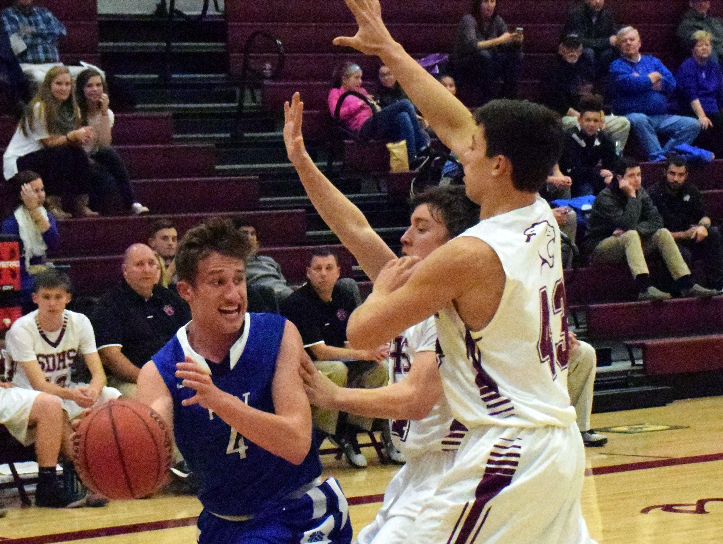Fort Defiance's Jacob Jones, left, passes around Stuarts Draft's Nick lasam, center, and Kasey Branch during the first half of their boys basketball game on Tuesday, Dec. 13, 2016, at Stuarts Draft High School in Stuarts Draft, Va.