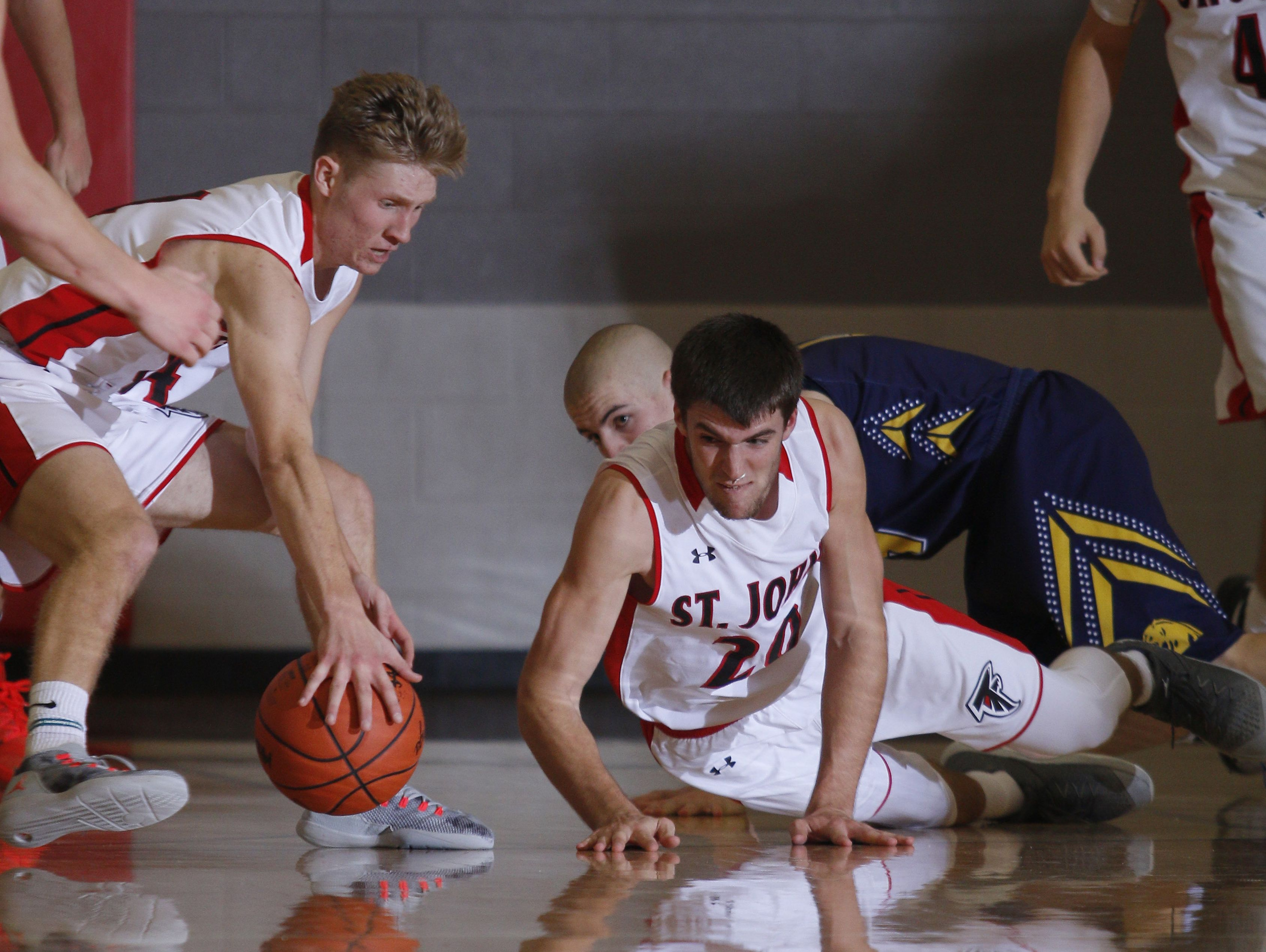 St. Johns' Brandon Huhn, left, and Ross Feldpausch (20) and DeWitt's Nathan Flannery, rear, chase a loose ball Friday, Dec. 16, 2016, in St. Johns, Mich. St. Johns won 53-44.