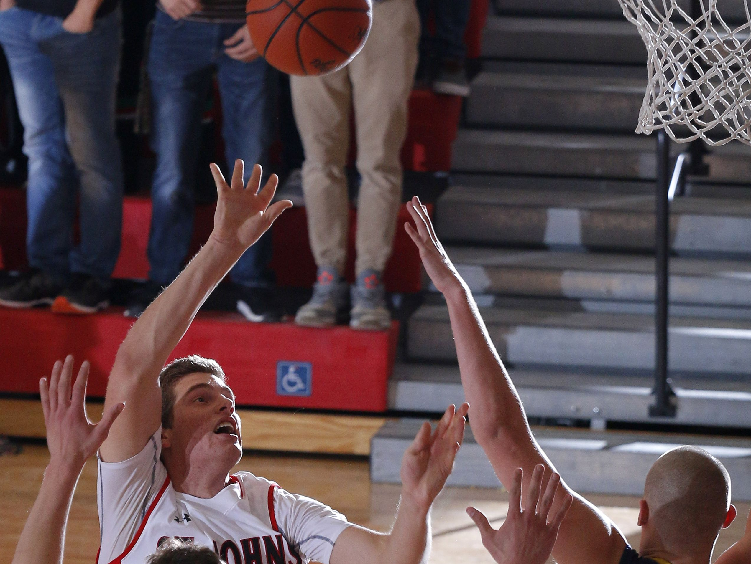 St. Johns' Caleb Paksi, left rear, shoots against DeWitt's Tanner Reha (44) and Luke Hyde (35) Friday, Dec. 16, 2016, in St. Johns, Mich.