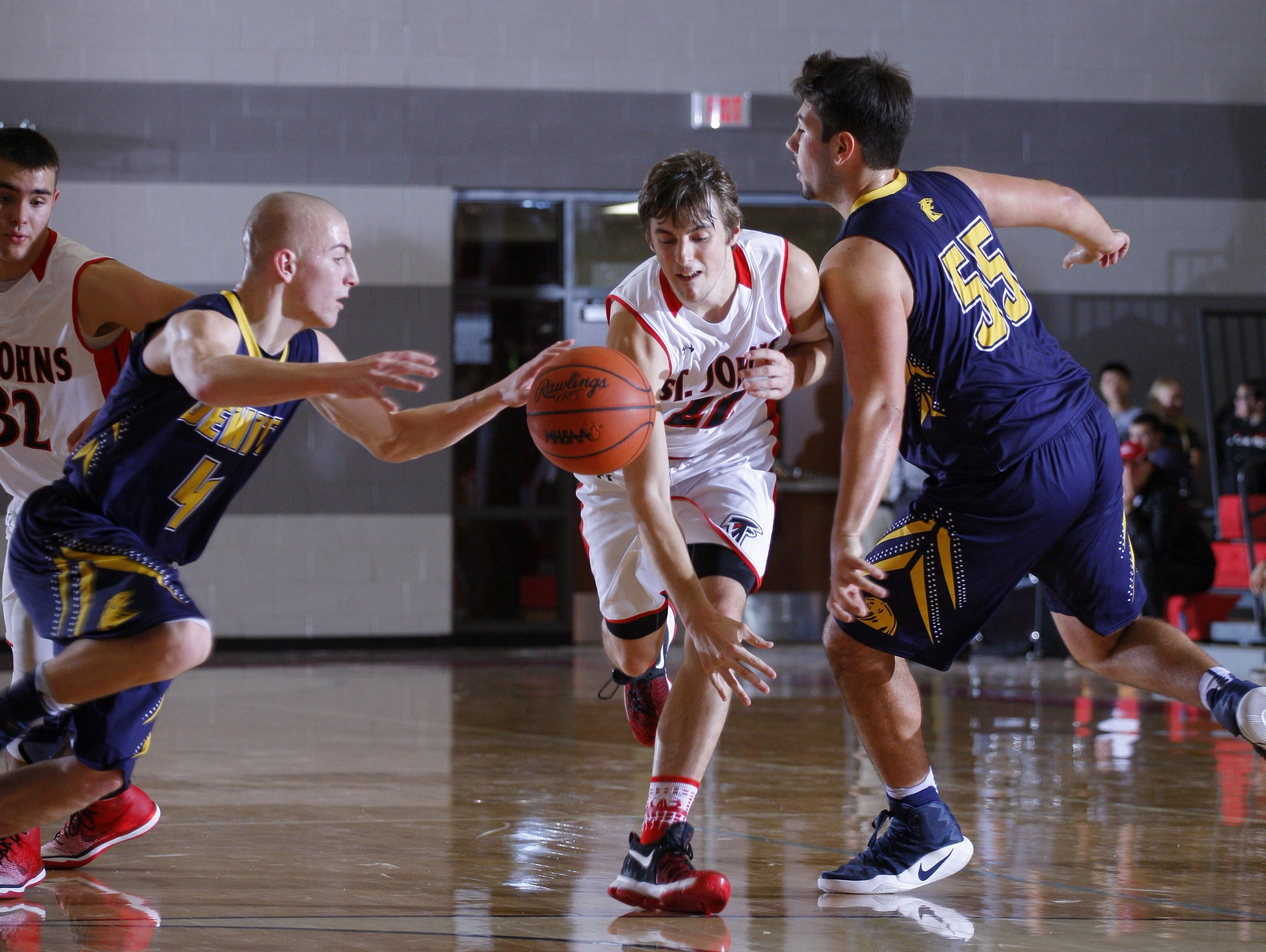 DeWitt's Nathan Flannery, left, and Alec Guillaume (55) and St. Johns' Ben Feldpausch, center, vie for the ball Friday, Dec. 16, 2016, in St. Johns, Mich.