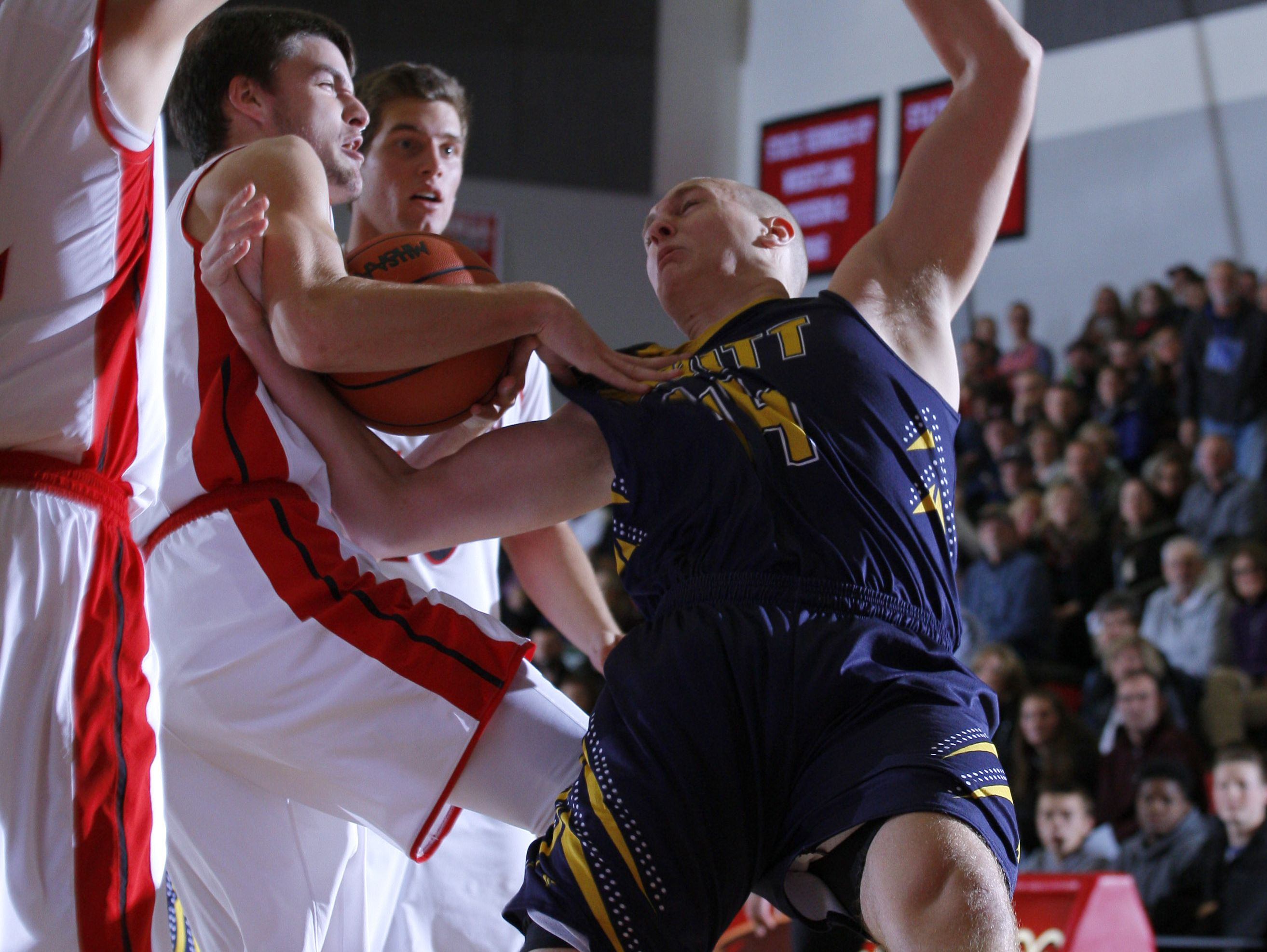 DeWitt's Tanner Reha, right, is fouled on a drive by St. Johns' Ross Feldpausch Friday, Dec. 16, 2016, in St. Johns, Mich.