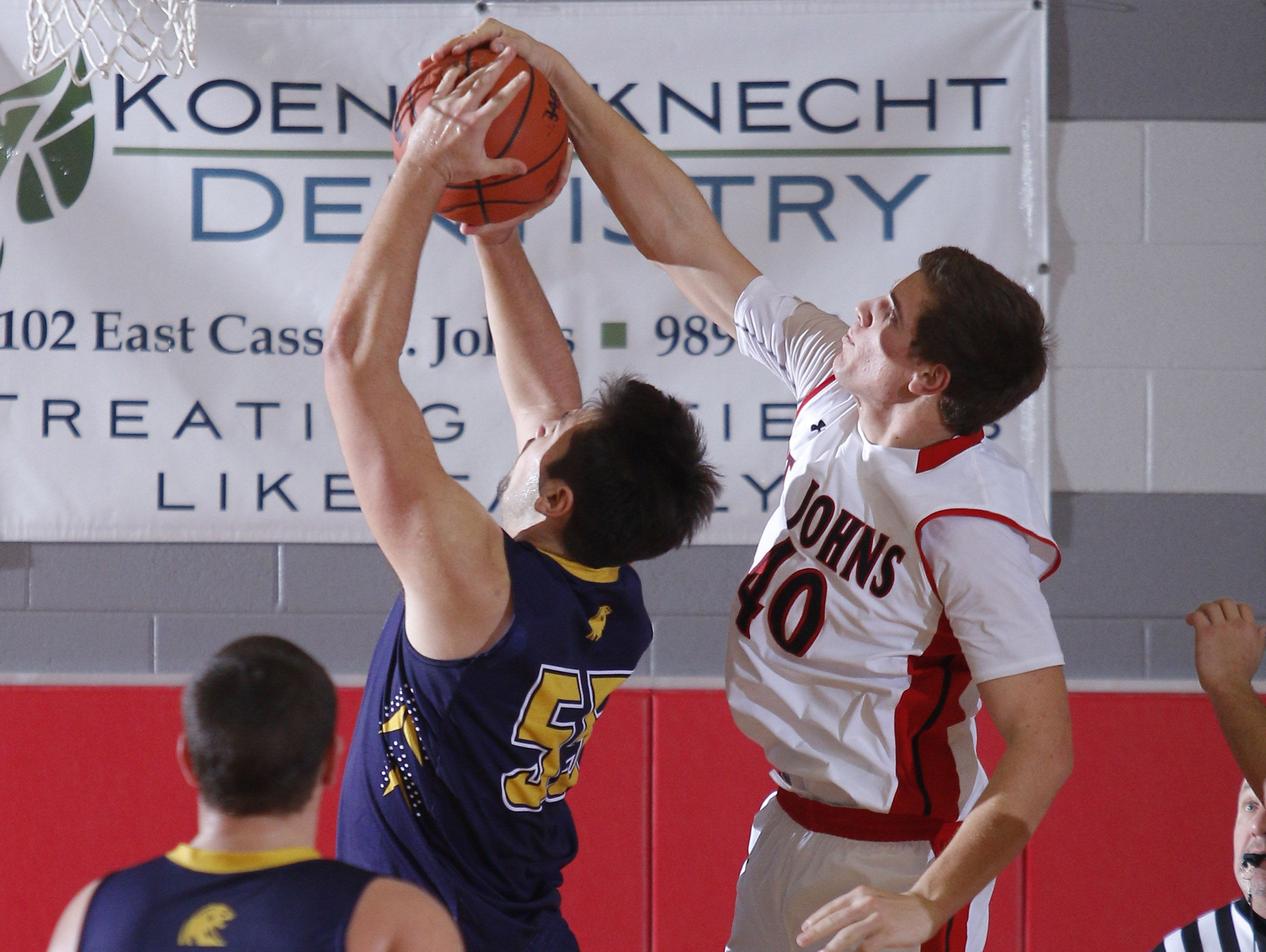 St. Johns' Caleb Paksi, right, blocks a shot by DeWitt's Alec Guillaume Friday, Dec. 16, 2016, in St. Johns, Mich.
