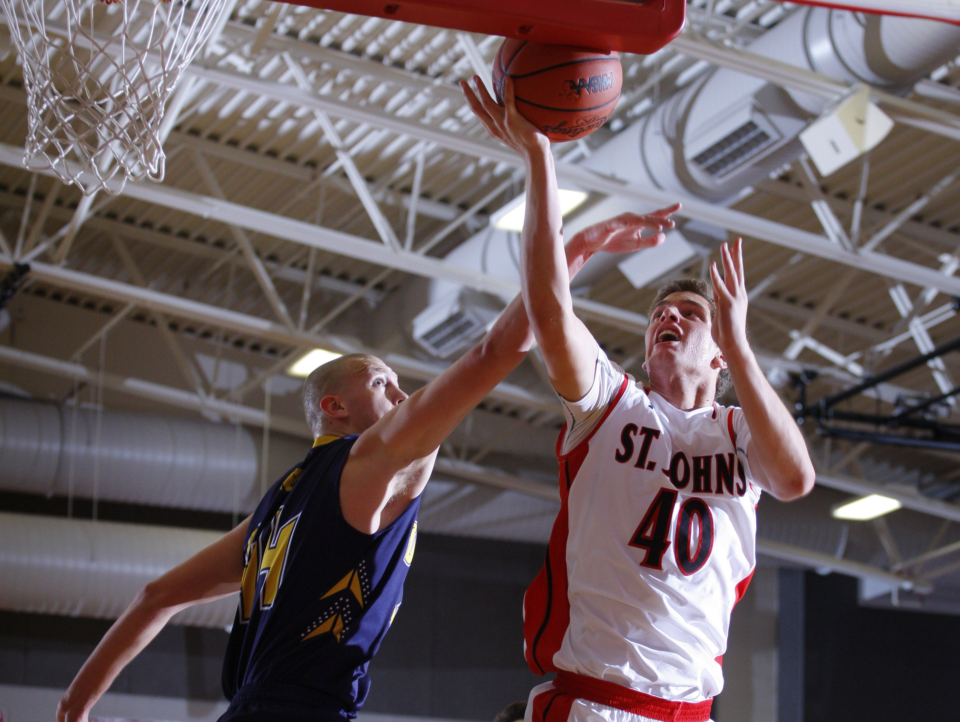 St. Johns' Caleb Paksi, right, goes up for a shot against DeWitt's Tanner Reha Friday, Dec. 16, 2016, in St. Johns, Mich.