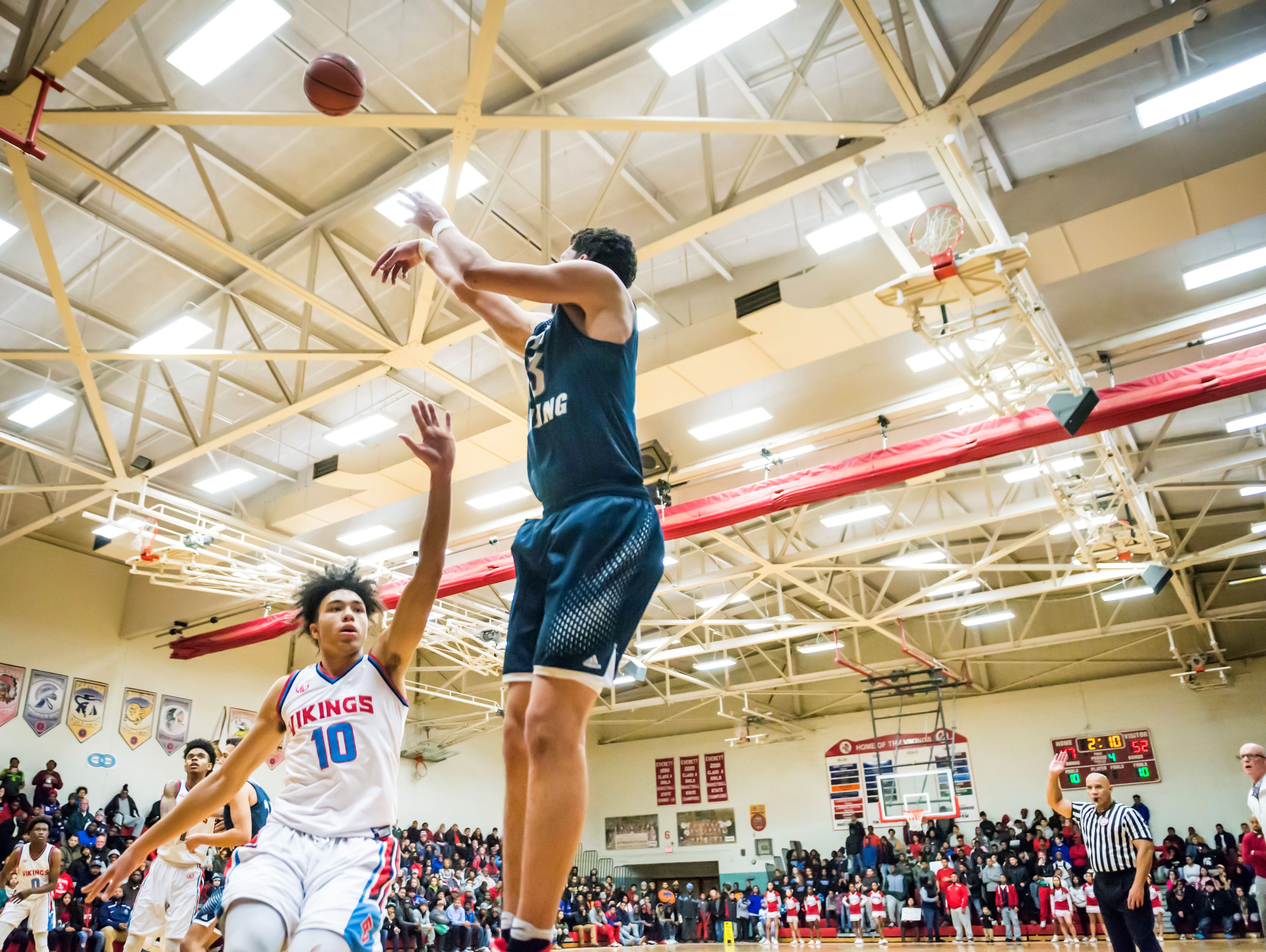 Brandon Johns, top, of East Lansing sinks a 3-point shot over Dante Walton ,10, of Everett with 2:10 remaining in the 4th quarter of their game to put East Lansing up 55-47 Friday, December 16, 2016 in Lansing.