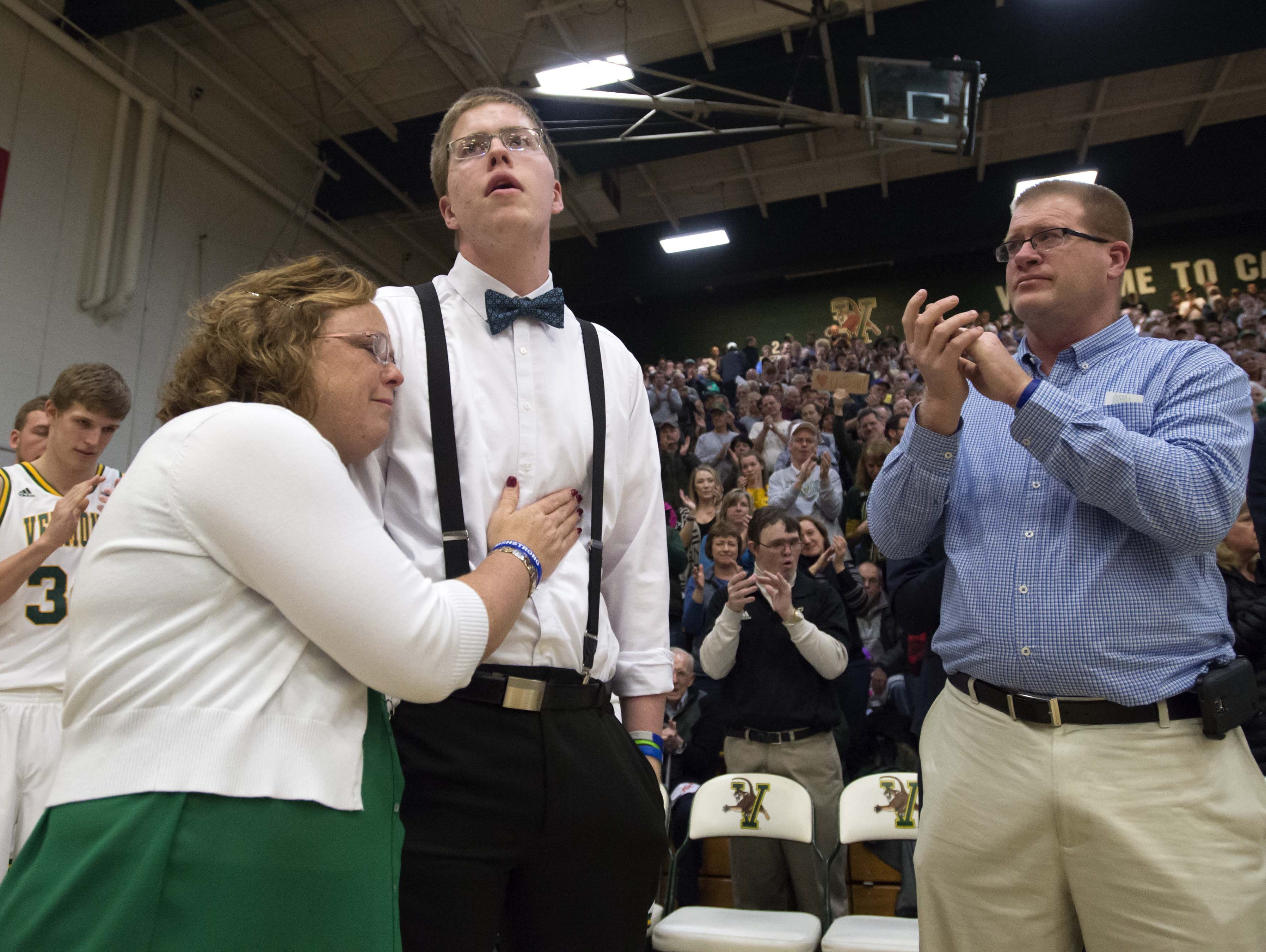 Josh Speidel gets a hug from his mother Lisa as his father Dave looks on as he is introduced before the start of the University of Vermont's game against Stony Brook, Jan. 30, 2016.