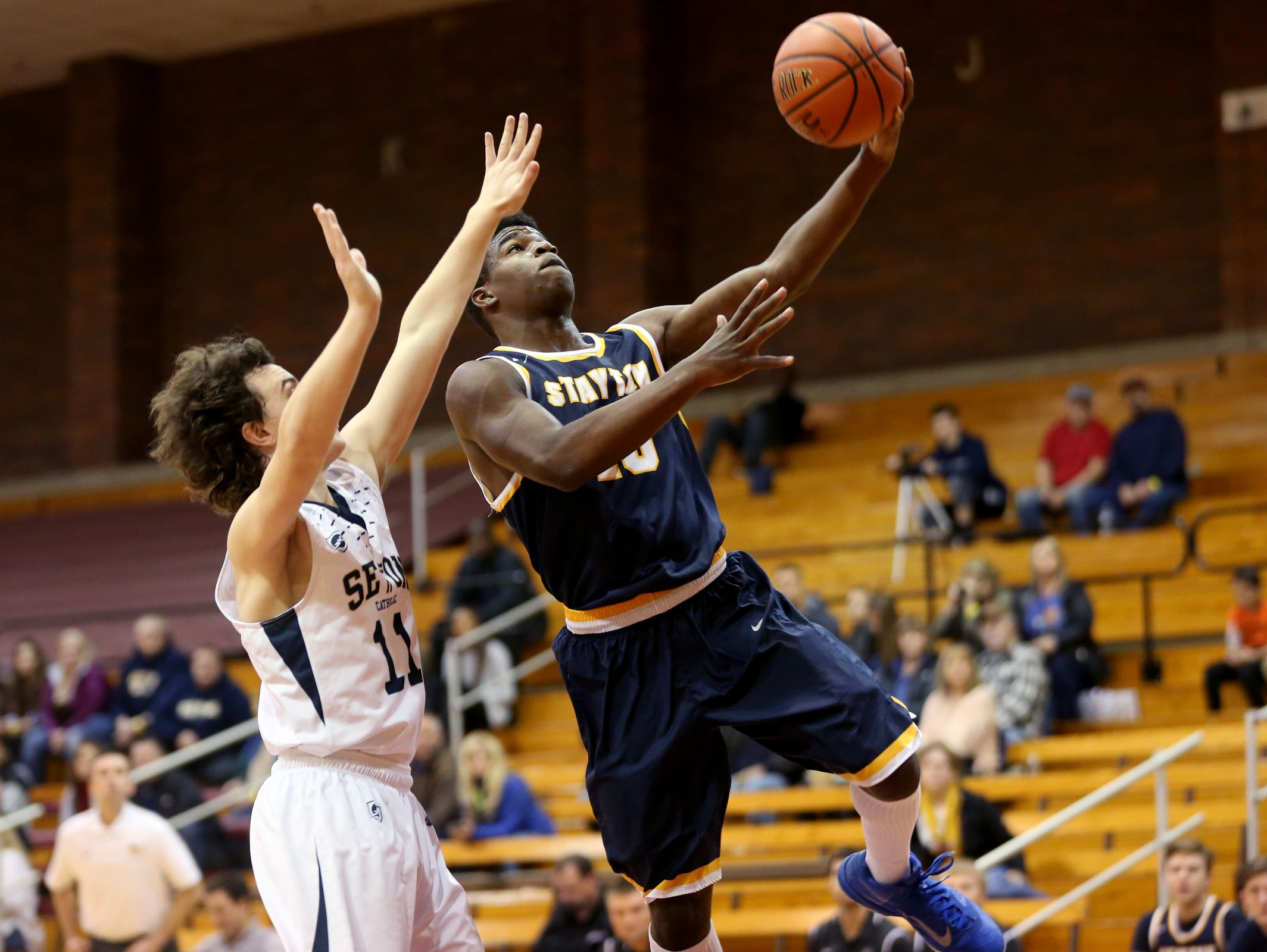 Stayton's Jerry Daniels (25) goes for a layup past Seton's Ben Owen (11) in the Stayton vs. Seton Catholic boy's basketball game on the first day of the Capitol City Classic tournament at Willamette University in Salem on Wednesday, Dec. 21, 2016. Stayton won the game 62-58.