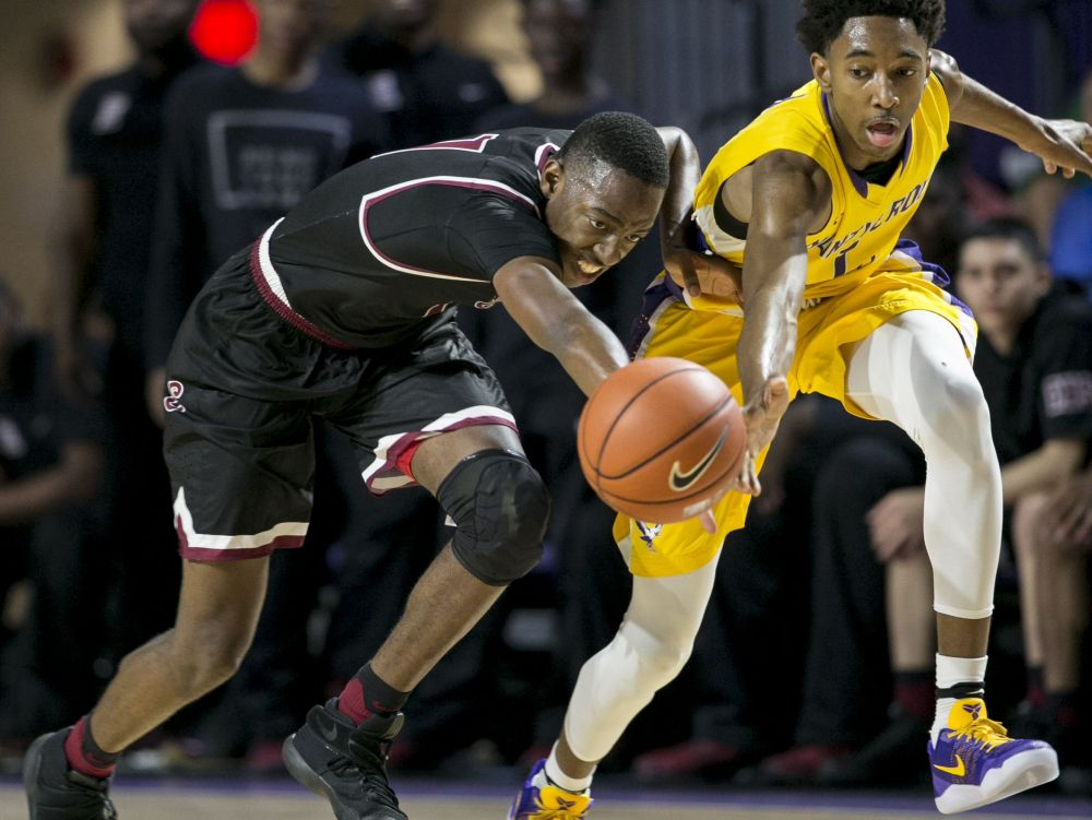 Memphis East's TJ Moss and Montverde Academy's Rechon Black lunge for the ball in the finals of the 44th Annual City of Palms Classic on Wednesday, December 21, 2016, at Suncoast Credit Union Arena in Fort Myers.