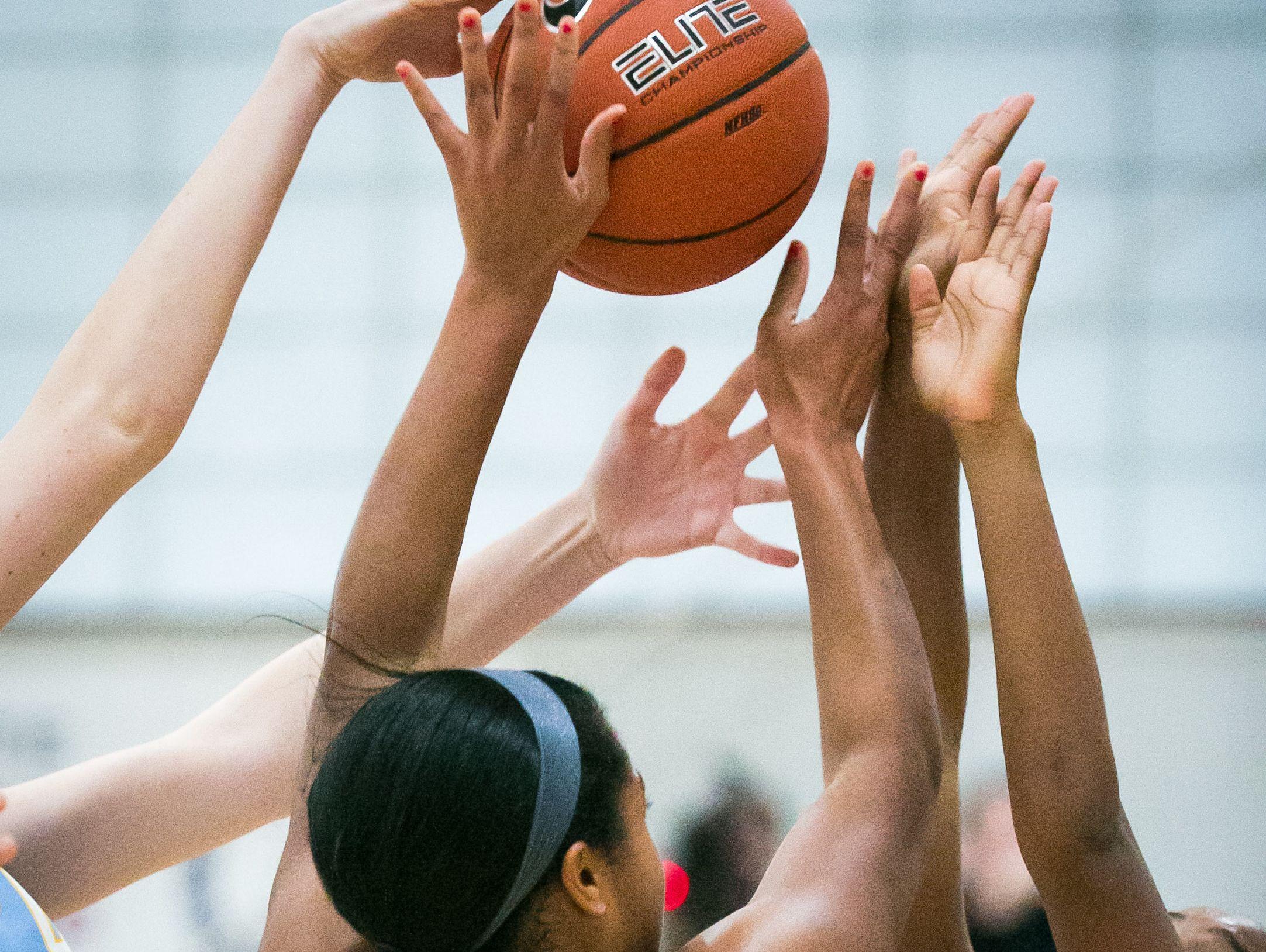 Wilmington Friends center Jayna Jones (center) battles for the rebound.