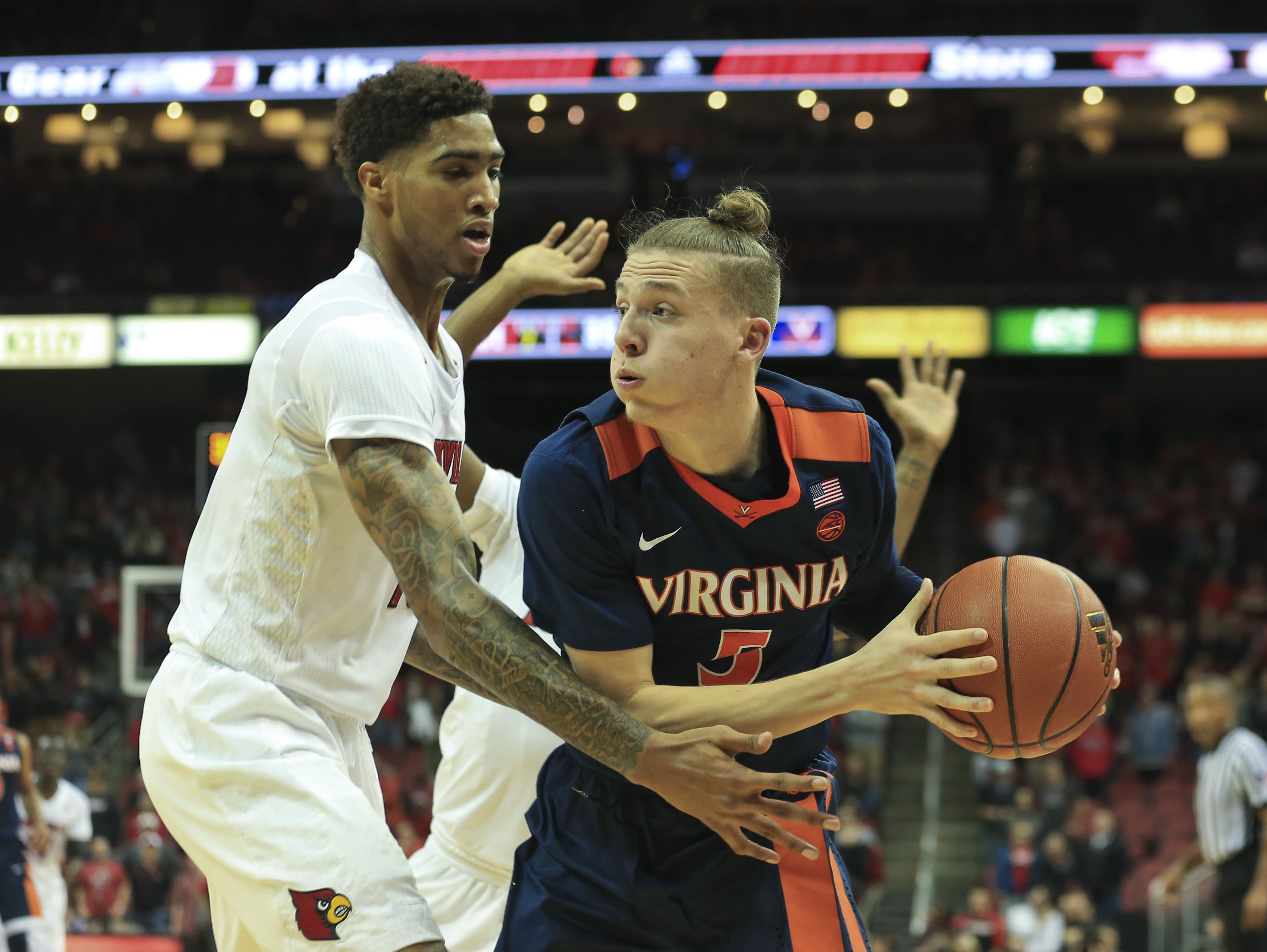 Virginia's Kyle Guy looks to pass as he's pressured by Louisville's Ray Spalding in the Cavaliers' win over the Cards 61-53 Wednesday night.