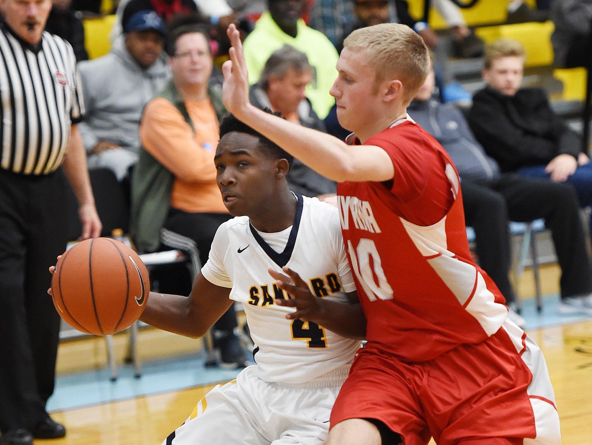 Sanford's Sean Williams (4) drives to the basket as Smyrna's Caleb Matthews defends.