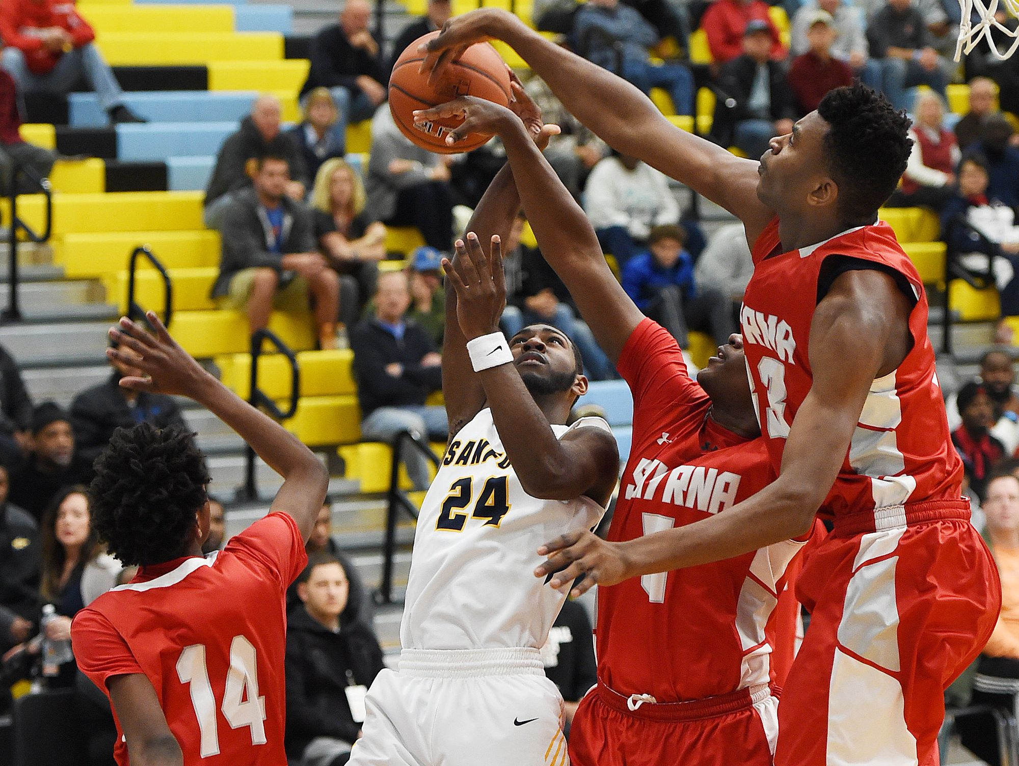 Sanford's Marcus McCollum (24) gets teamed up on by Smyrna players during Thursday action at the Slam Dunk to the Beach, held at Cape Henlopen.