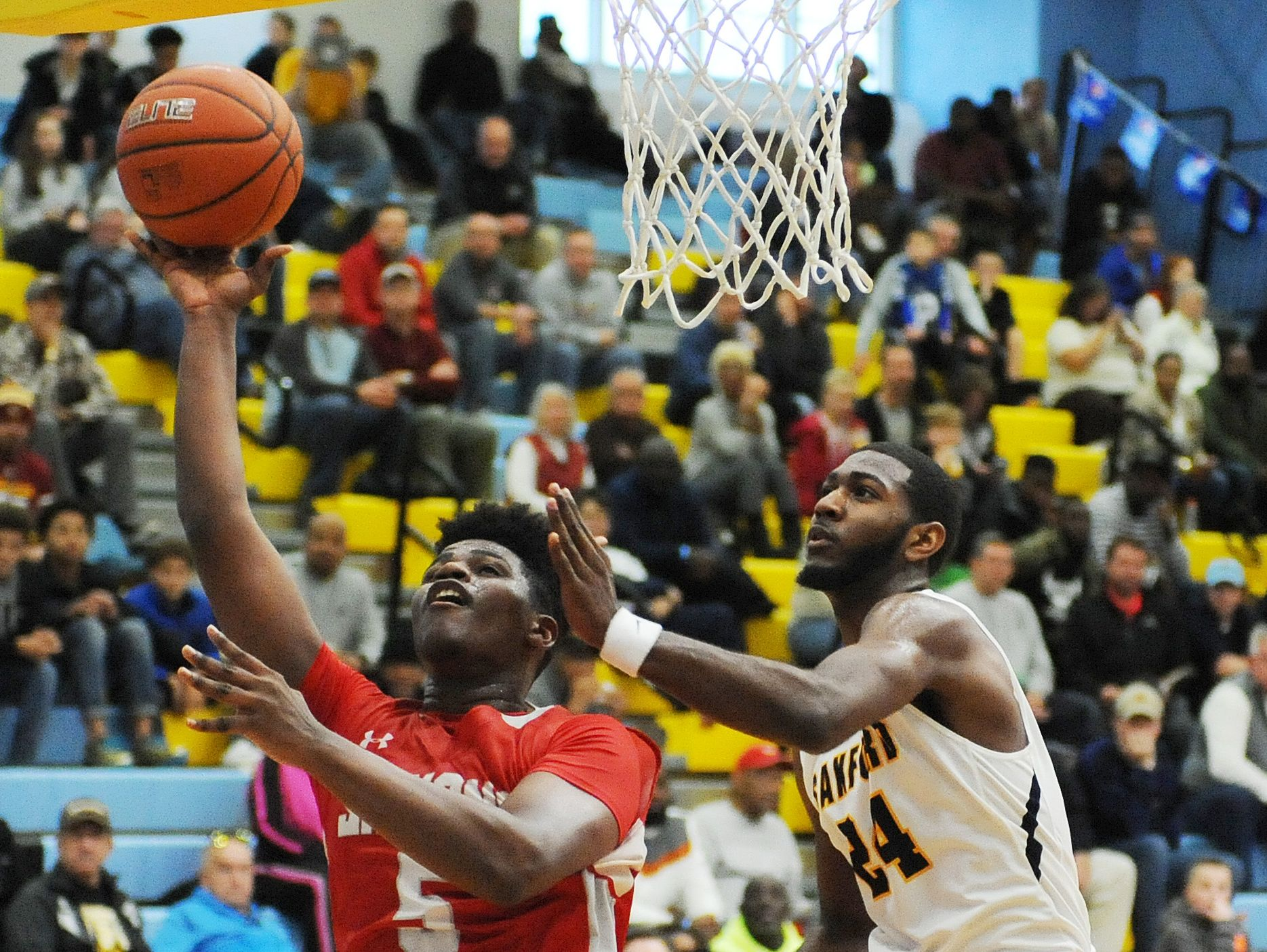 Smyrna's Jaymeir Garnett (5) makes a basket over Sanford's Marcus McCollum.