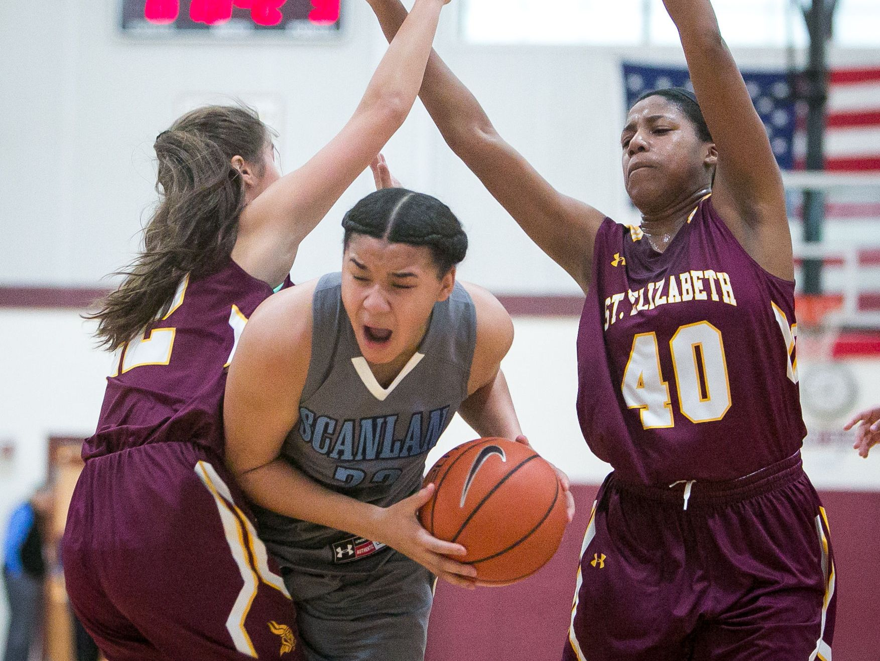 St. Elizabeth senior, Lexi Bromwell (left), and teammate Alexis Lee pressures Monsignor Scanlan guard, Kateri Poole, who tries to squeeze through the two defenders.