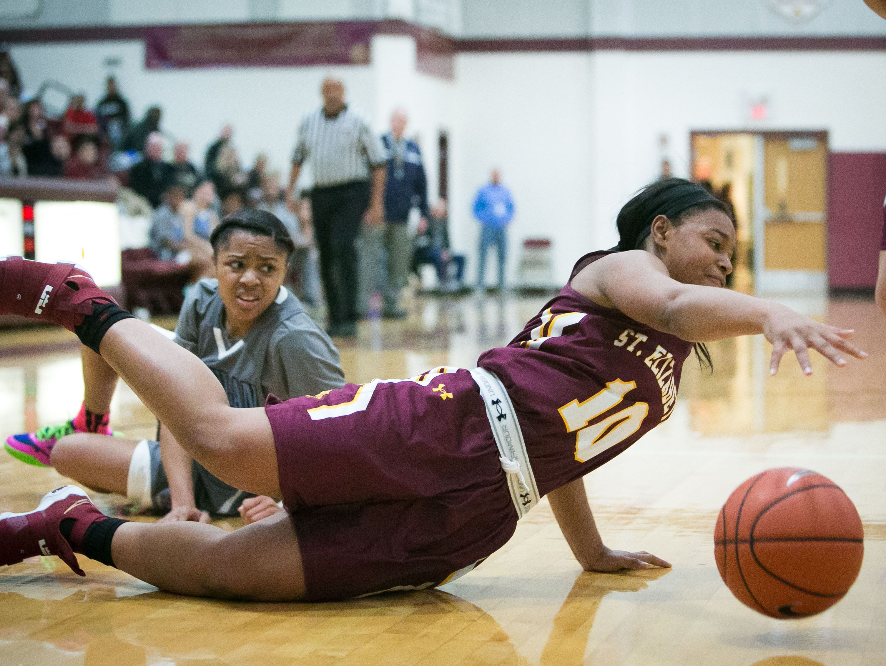 St. Elizabeth guard Sha'Nia Davis gets tripped up driving to the basket late in the game with no fouled called as they lose to Monsignor Scanlan with a final score of 53-44 in the Diamond State Classic at St. Elizabeths School.
