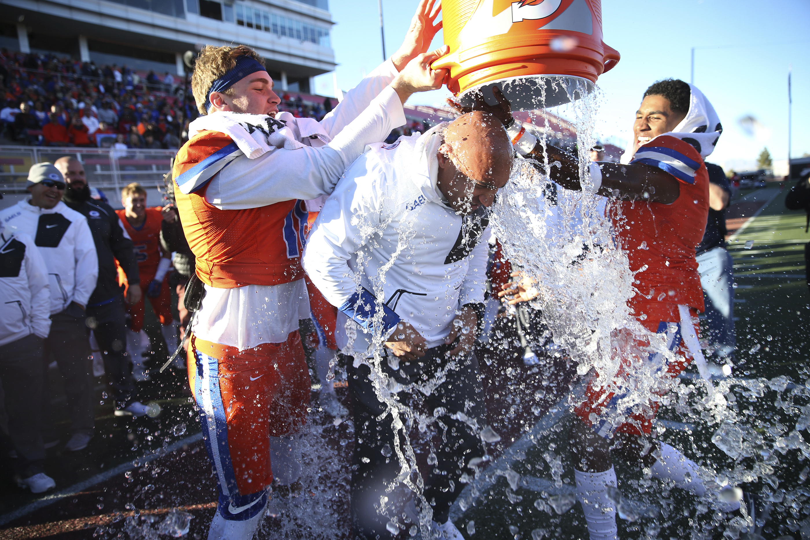 Bishop Gorman coach Kenny Sanchez, center, is doused by players Tate Martell, left, and Alex Perry (4) at the end of the Class 4A state football championship game against Liberty on Saturday, Dec. 3, 2016, in Las Vegas. (Erik Verduzco/Las Vegas Review-Journal via AP) ORG XMIT: NVLAS107
