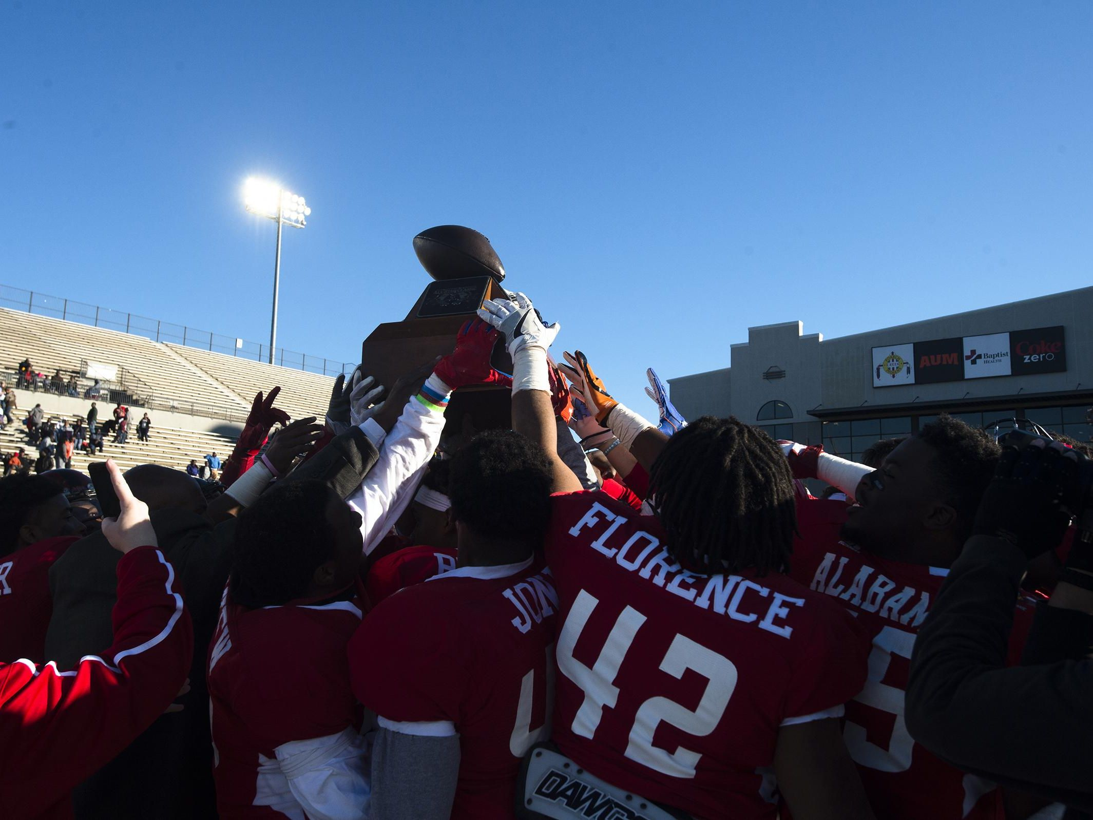 The Alabama All-Stars lift up the trophy after they defeated Mississippi 25-14.