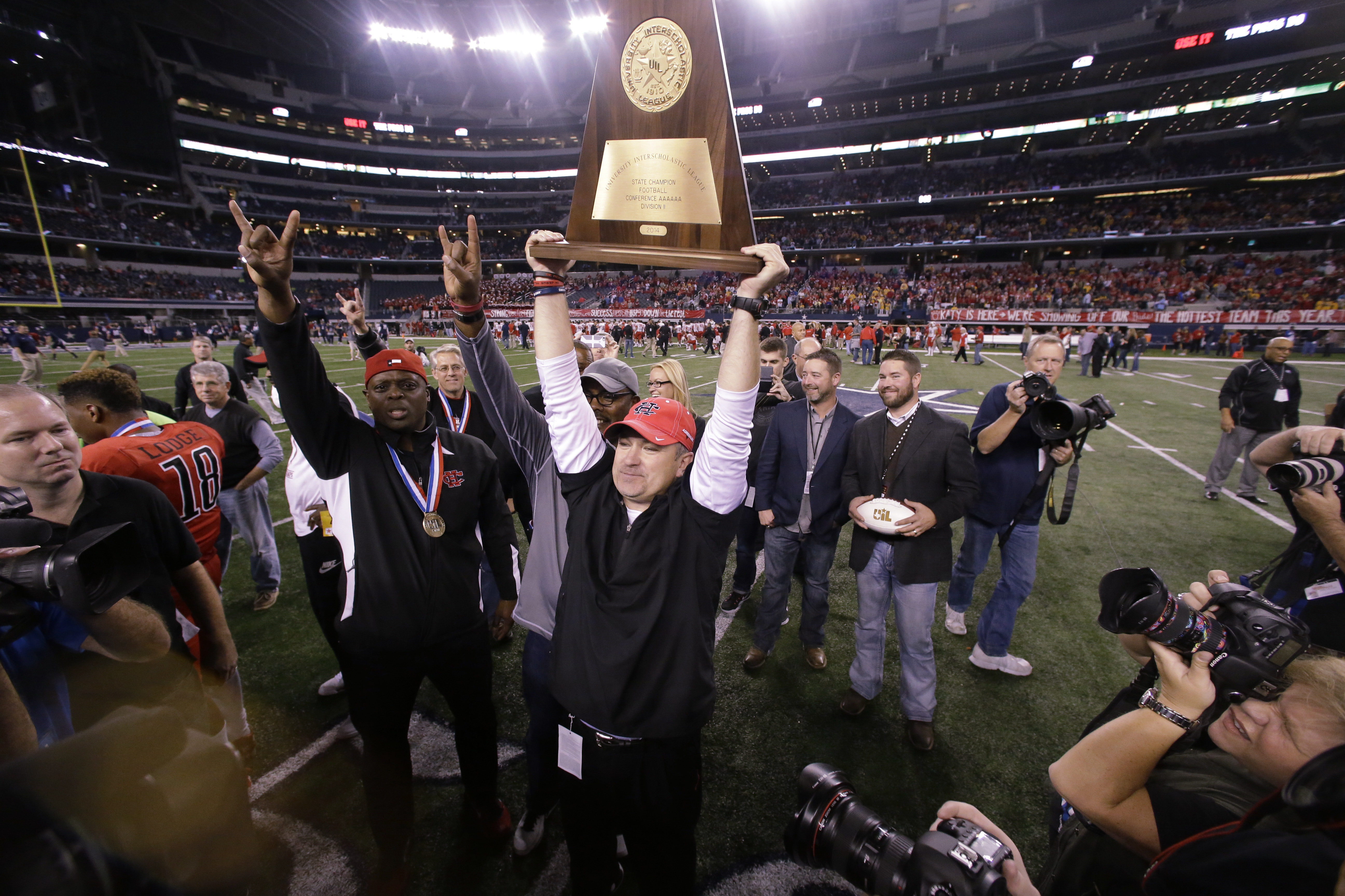Cedar Hill head coach Joey McGuire holds up the trophy after his team won the UIL 6A Division II State Championship football game. Cedar Hill won 23-20. (LM Otero, AP Photo)