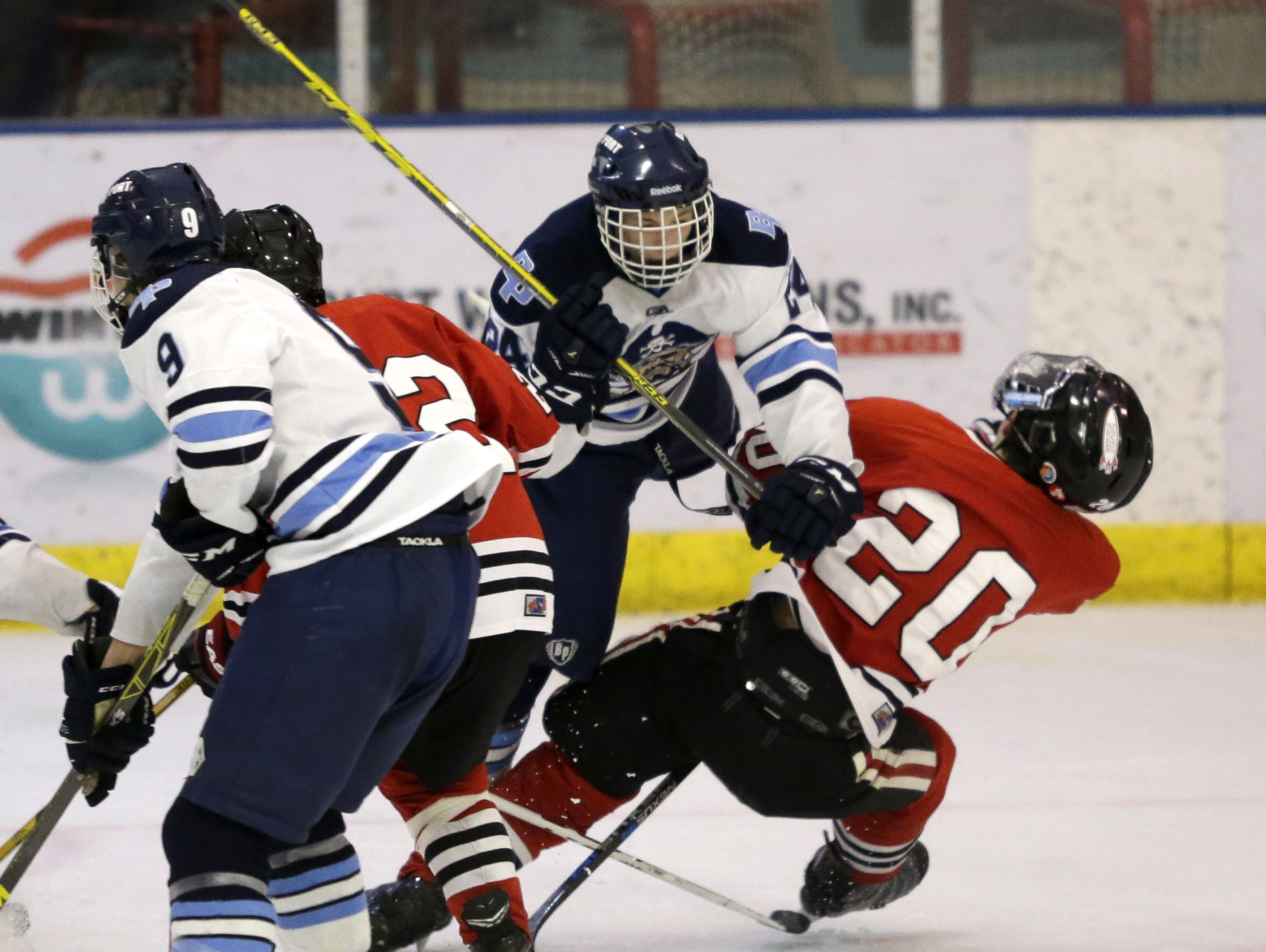 Bay Port's Spencer Kring delivers a hit to NHM's Max Hackinson during a boys hockey game last year. Kring had a game-winning goal in overtime Saturday over the co-op team.
