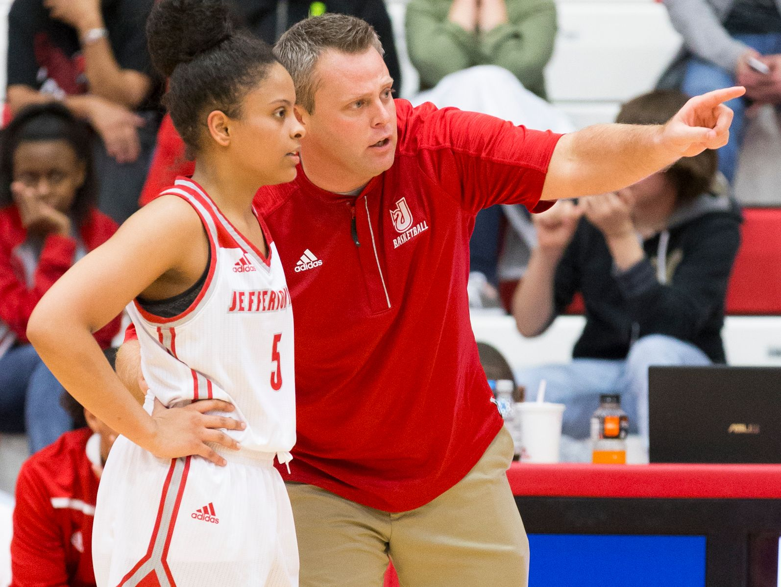 Jeffersonville head coach Mike Warren shares a teaching moment with Jasmine Lilly (5) during a game against Floyd Central at Jeffersonville.