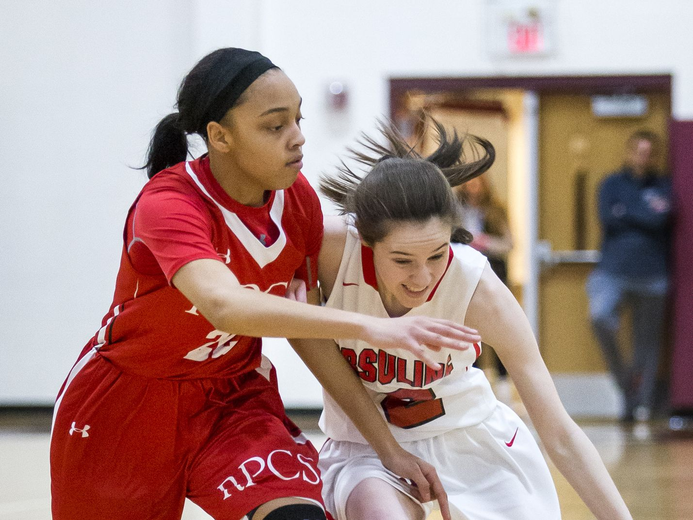Ursuline's Maggie Connolly (right) drives to the basket against Roland Park's Aniyah Carpenter at the Diamond State Classic in December.