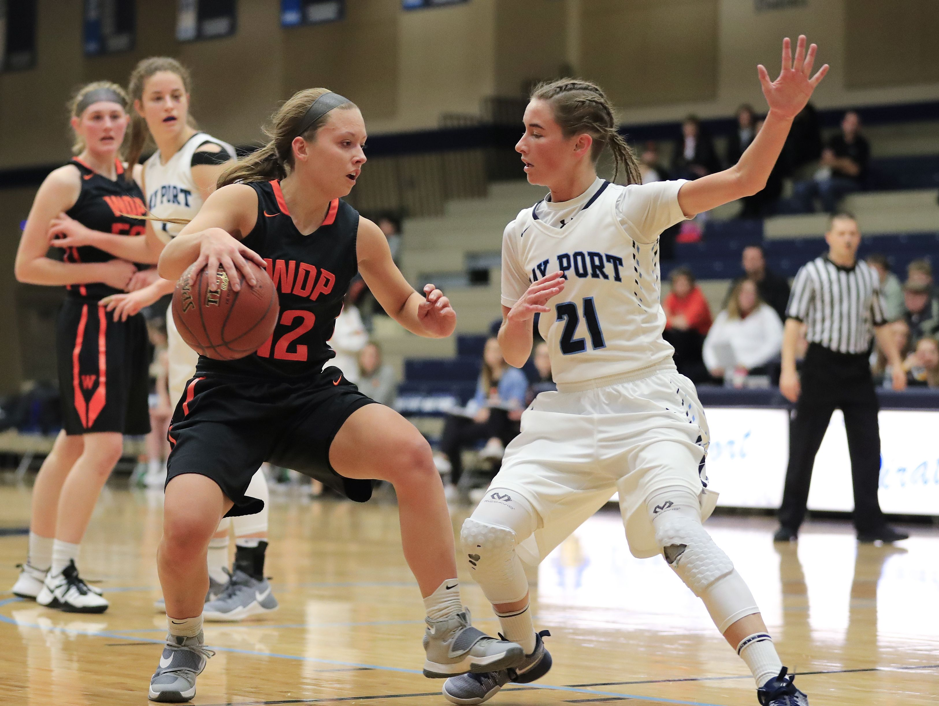 Bay Port's Meg Knutson (21) defends against West De Pere's Liz Edinger (12) on Dec. 30 at Bay Port during a nonconference game. Edinger has helped the Phantoms climb the state ranking and maintain a 3.83 team GPA.
