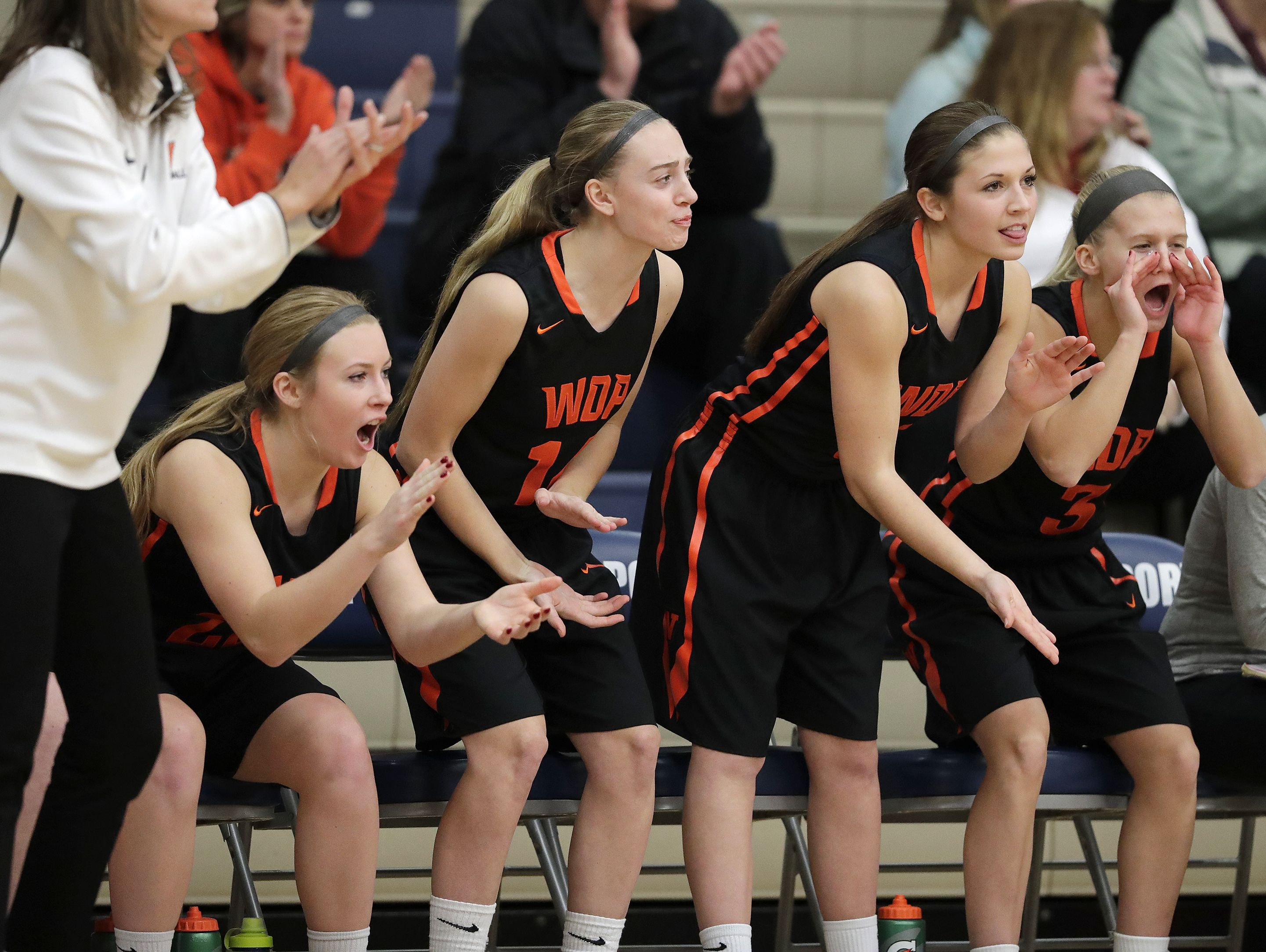West De Pere girls basketball players Kaeli Raasch (left to right), Kasey Denis, Sydney Appleton and Caroline Kandravi cheer during a nonconference game on Dec. 30 at Bay Port. The Phantoms earned academic all-state honors last season and have a 3.83 GPA this year.