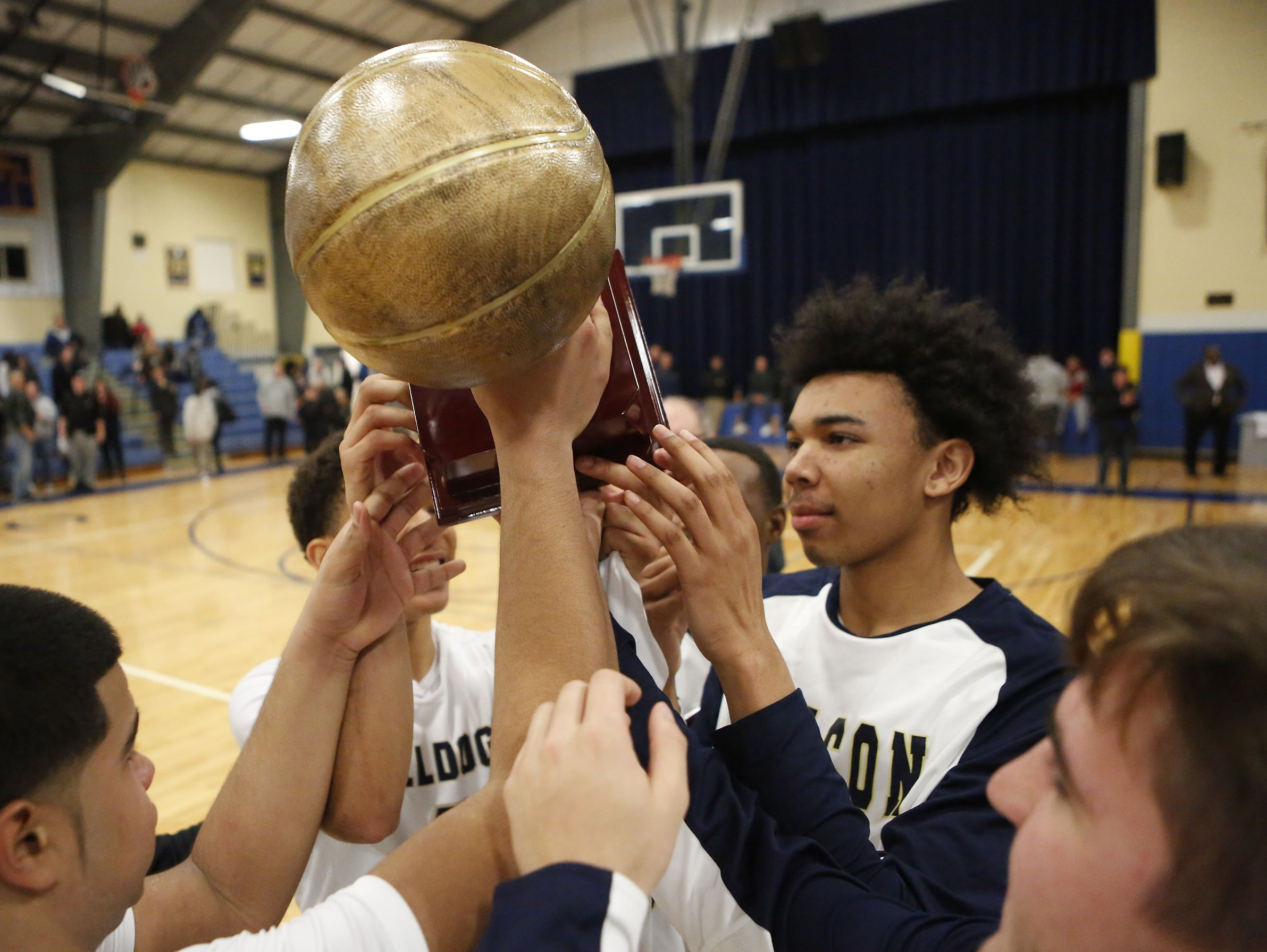 Beacon players hoist the trophy after defeating Spackenkill 76-64 in the championship game of the Duane Davis memorial basketball tournament at Our Lady of Lourdes High School in Poughkeepsie on Saturday, December 31, 2016.