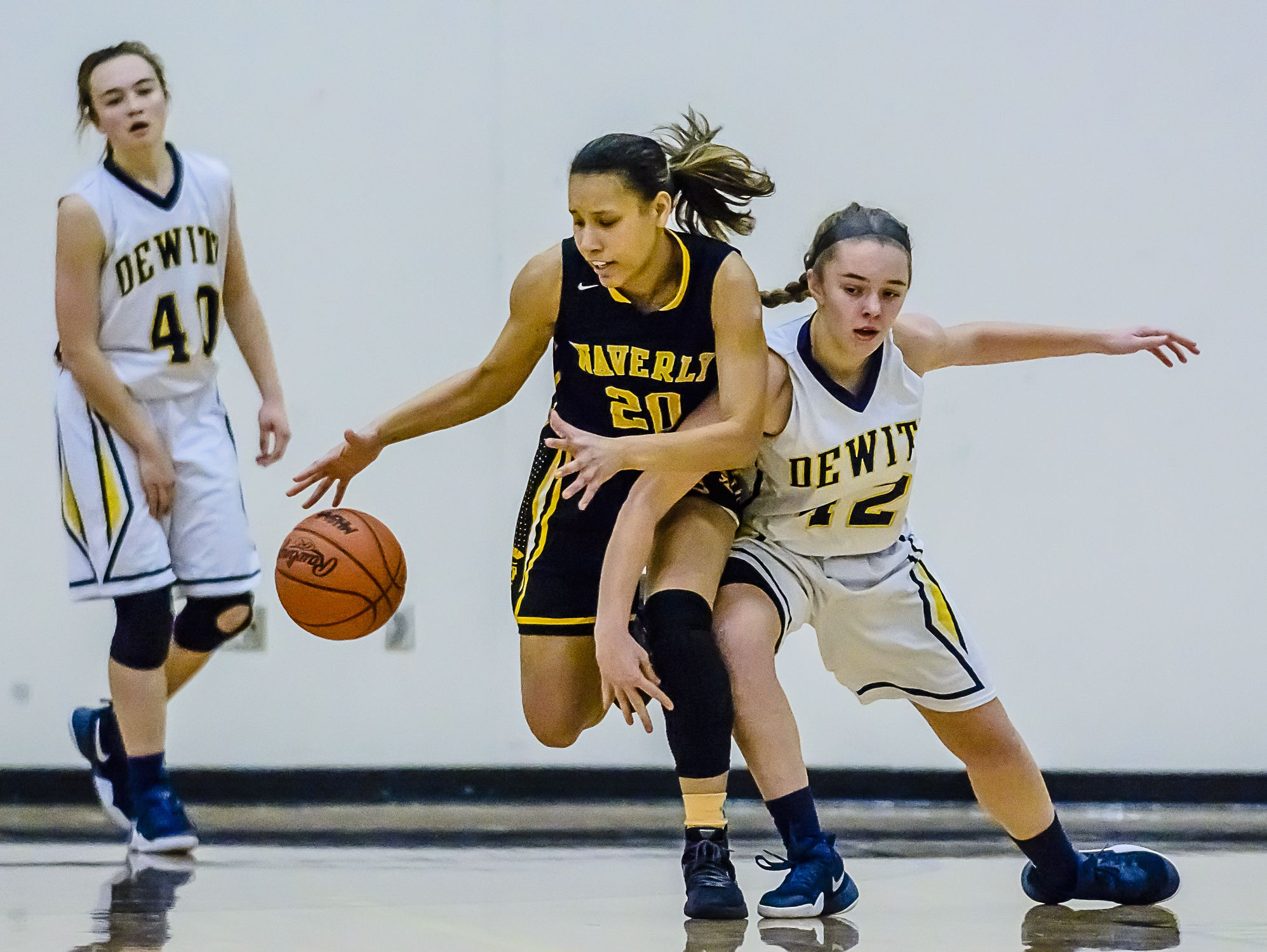 Evelyn Taylor ,center, of Waverly scoops up the ball for a turnover after Lily Stephan of DeWitt losses control in the 3rd quarter of their game Friday January 6, 2017 in DeWitt. KEVIN W. FOWLER PHOTO