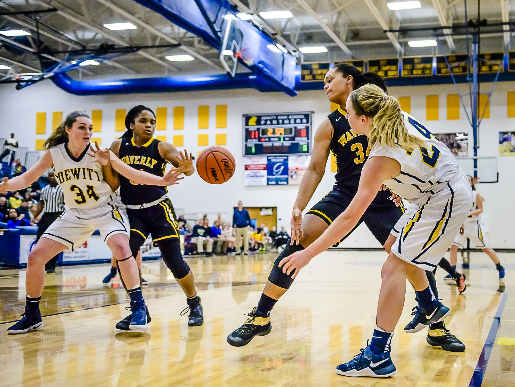 Annie MacIntosh ,right, of DeWitt passes around Malin Smith of Waverly to teammate Grace George ,34, in the paint during their game Friday January 6, 2017 in DeWitt. KEVIN W. FOWLER PHOTO