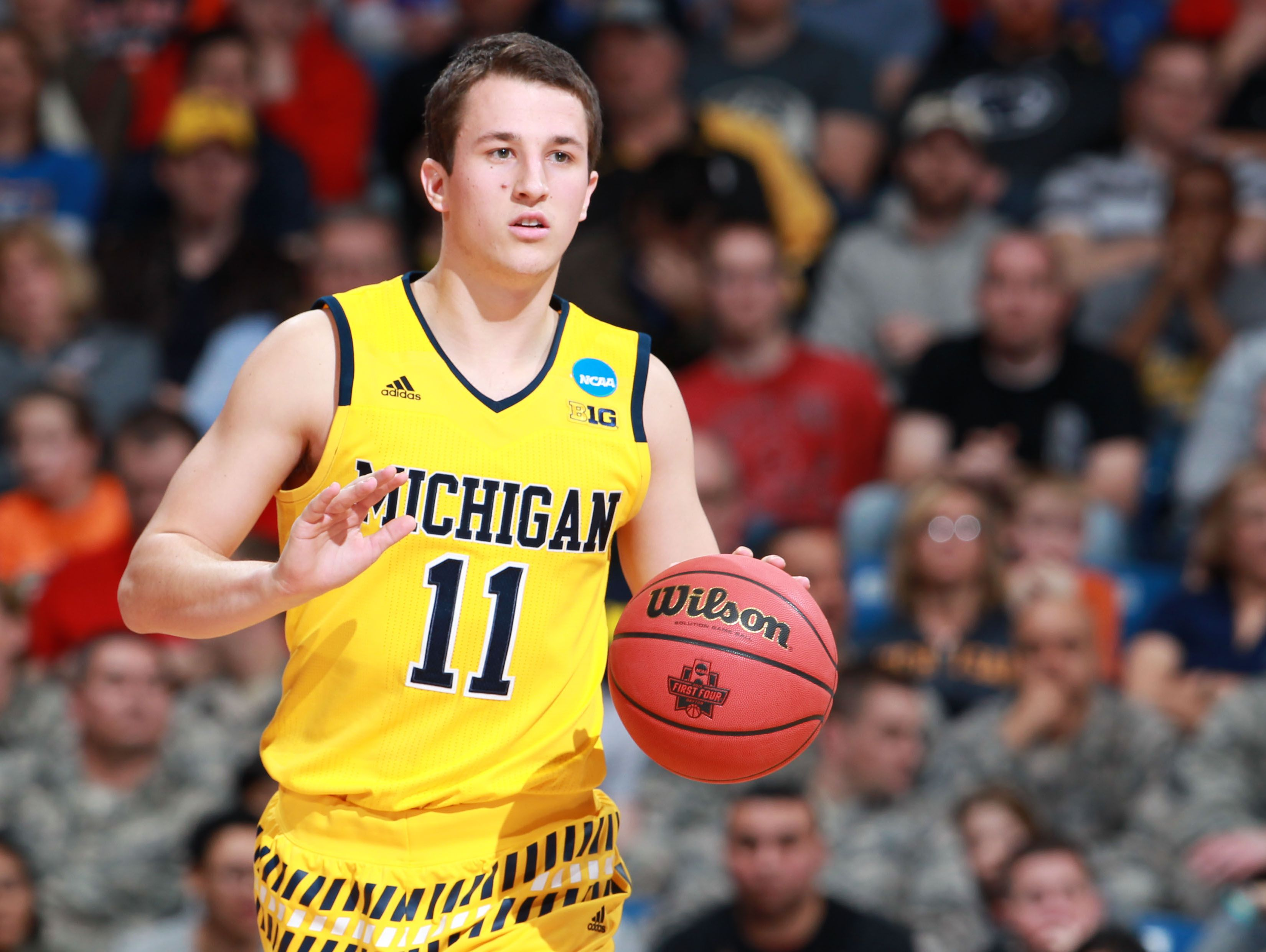Michigan Wolverines guard Andrew Dakich (11) brings the ball up court during the first half against the Tulsa Golden Hurricane in the First Four of the NCAA men's college basketball tournament at Dayton Arena.