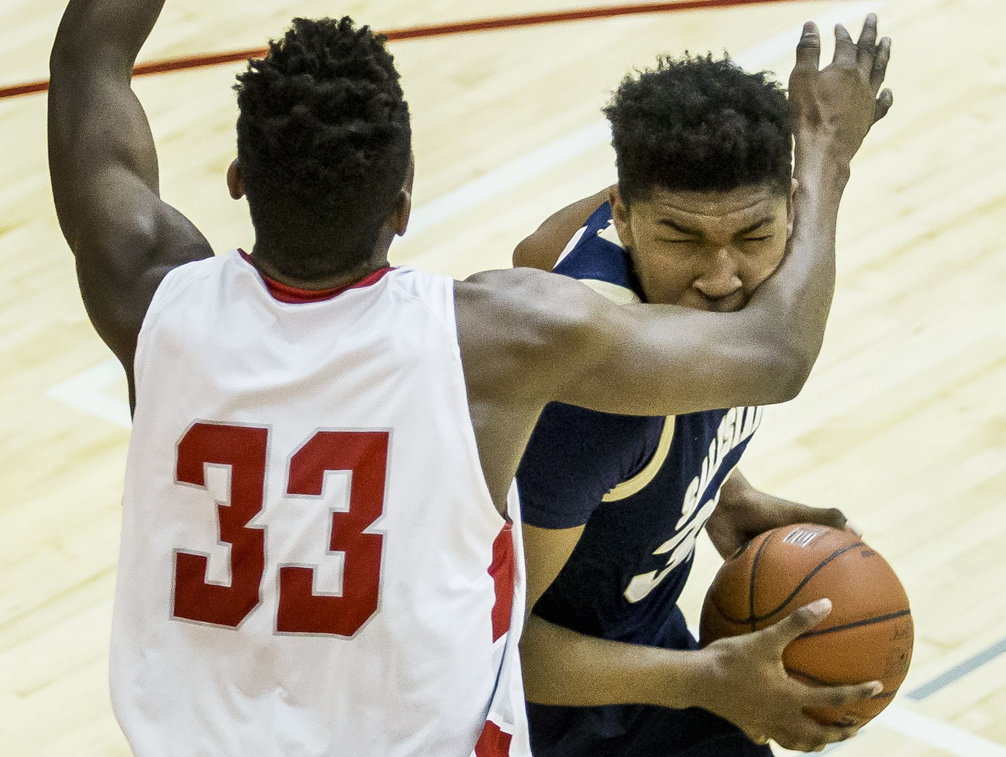 Salesianum's Tariq Ingraham takes a forearm to the face from Smyrna's Azubuike Nwankwo in the first half of Smyrna's 53-40 win over Salesianum at Smyrna High School on Tuesday night.