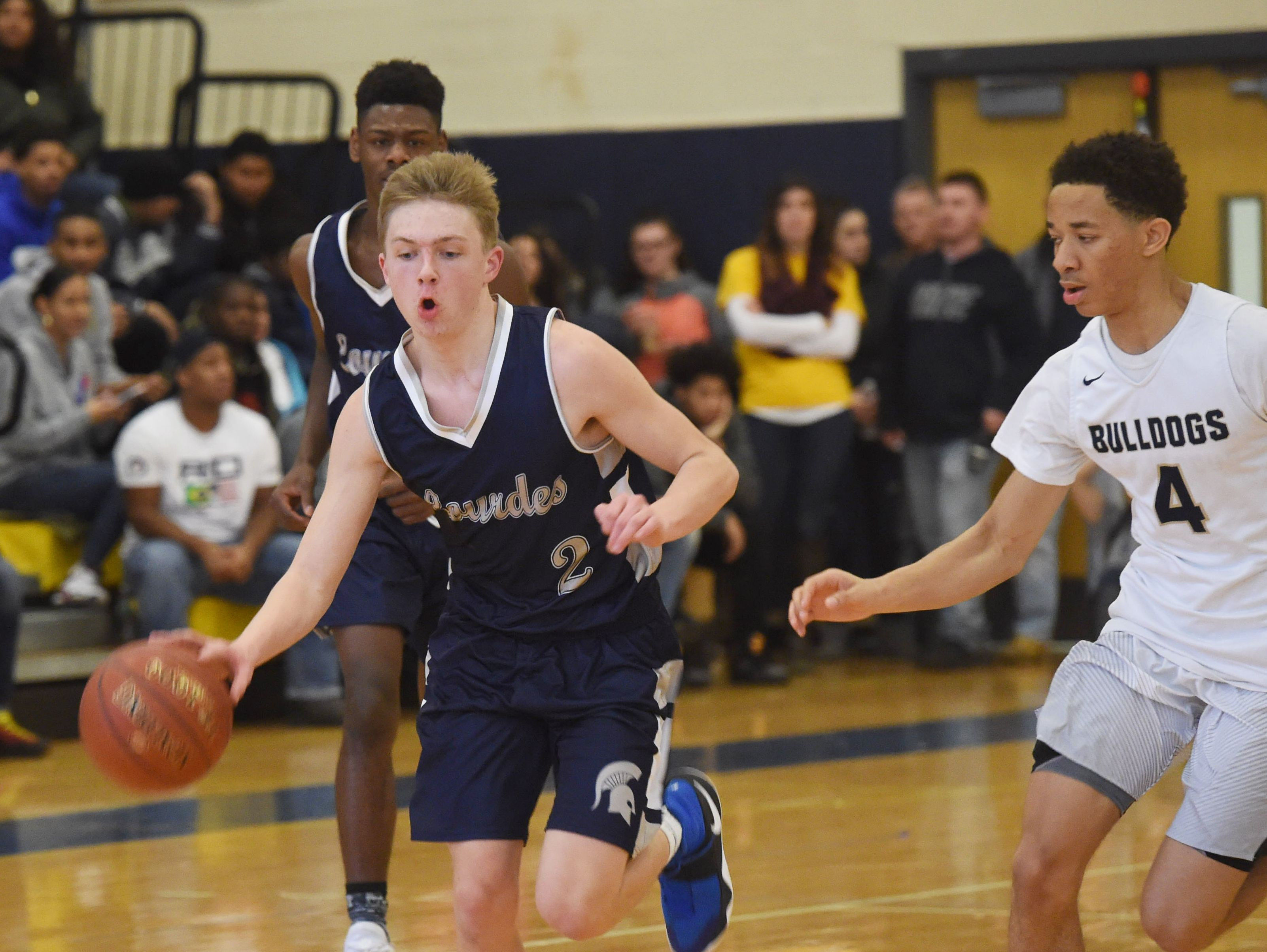 Our Lady of Lourdes' Joe Heavey, left, takes the ball down the court as Beacon's Brandon Evans, right, defends during a Jan. 14 game.