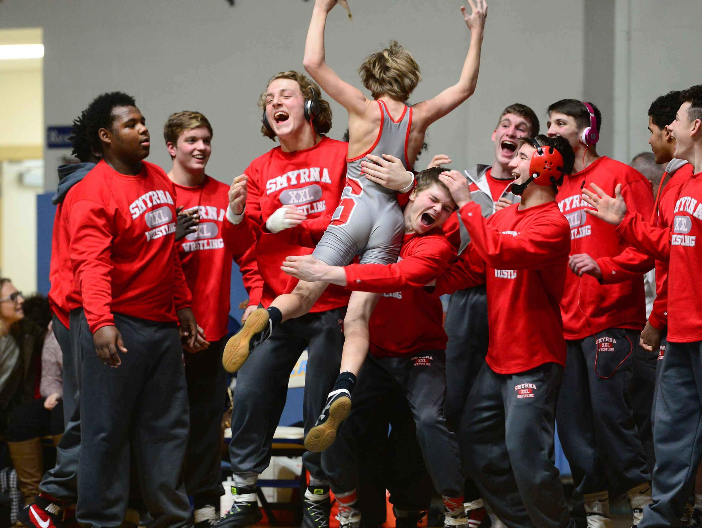 Smyrna's Dylan Andruzzi celebrates with his teammates after winning his first match of the year during the 106lb match up against Keith Harmon at Cape Henlopen High School on Wednesday, Jan. 18, 2017.