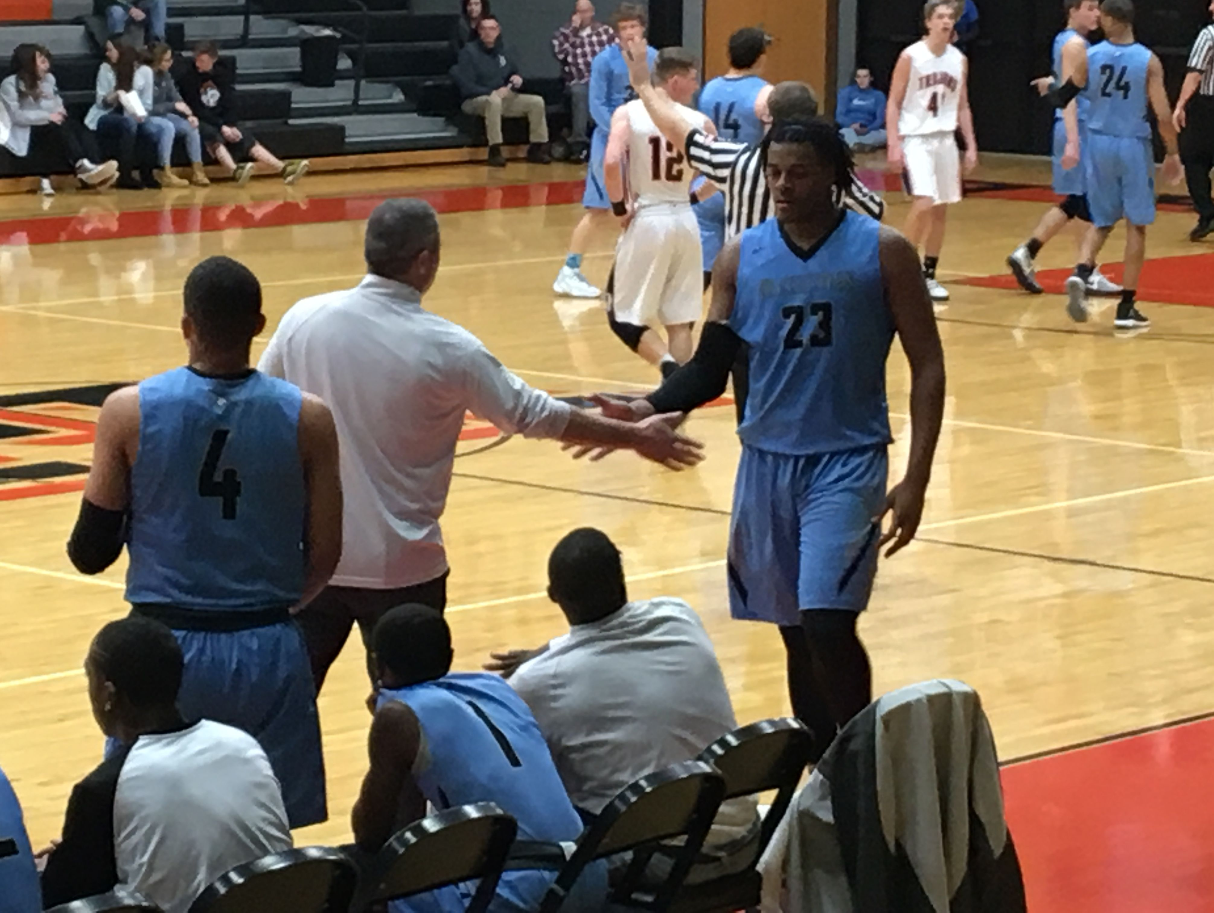 Xavier Tillman slaps five with Grand Rapids Christian head coach Mark Warners as he exits Friday's win over Thornapple-Kellogg in Middleville.
