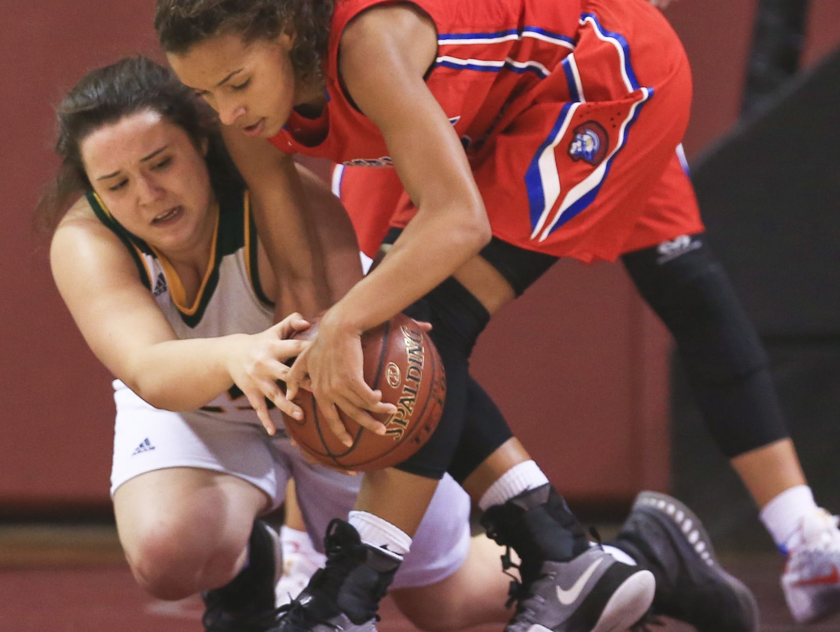CAL's Shelby Calhoun tussles with North Bullitt's Caroline Janes in the first game of the Girls' LIT at Bellarmine University. The Lady Centurions beat the Lady Eagles 57-45.