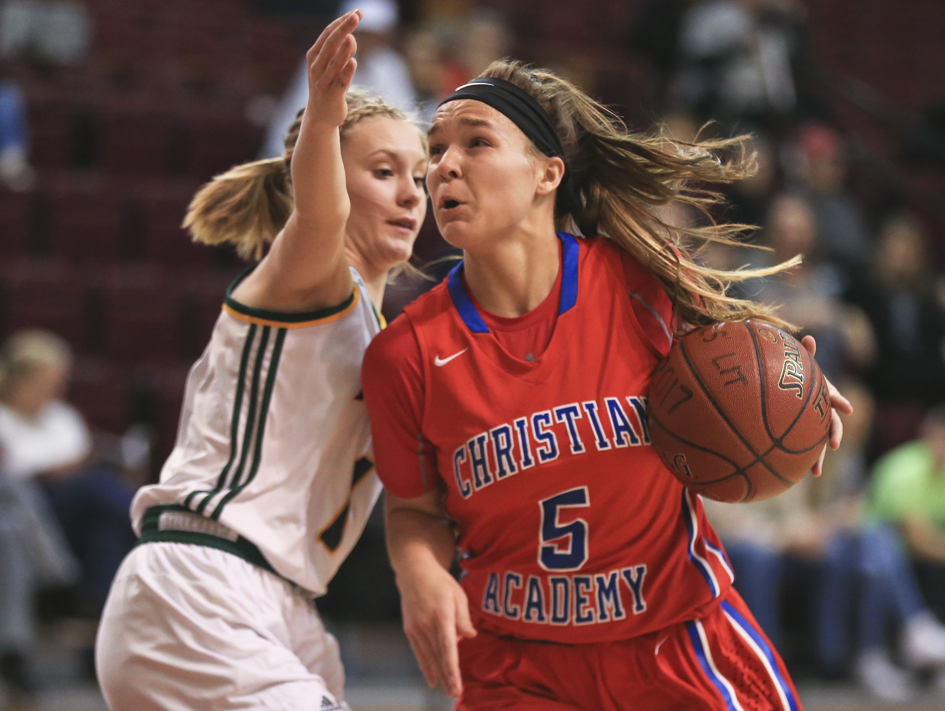 CAL's Emma Wesley drives past North Bullitt's Hailey Free in the first game of the Girls' LIT at Bellarmine University.