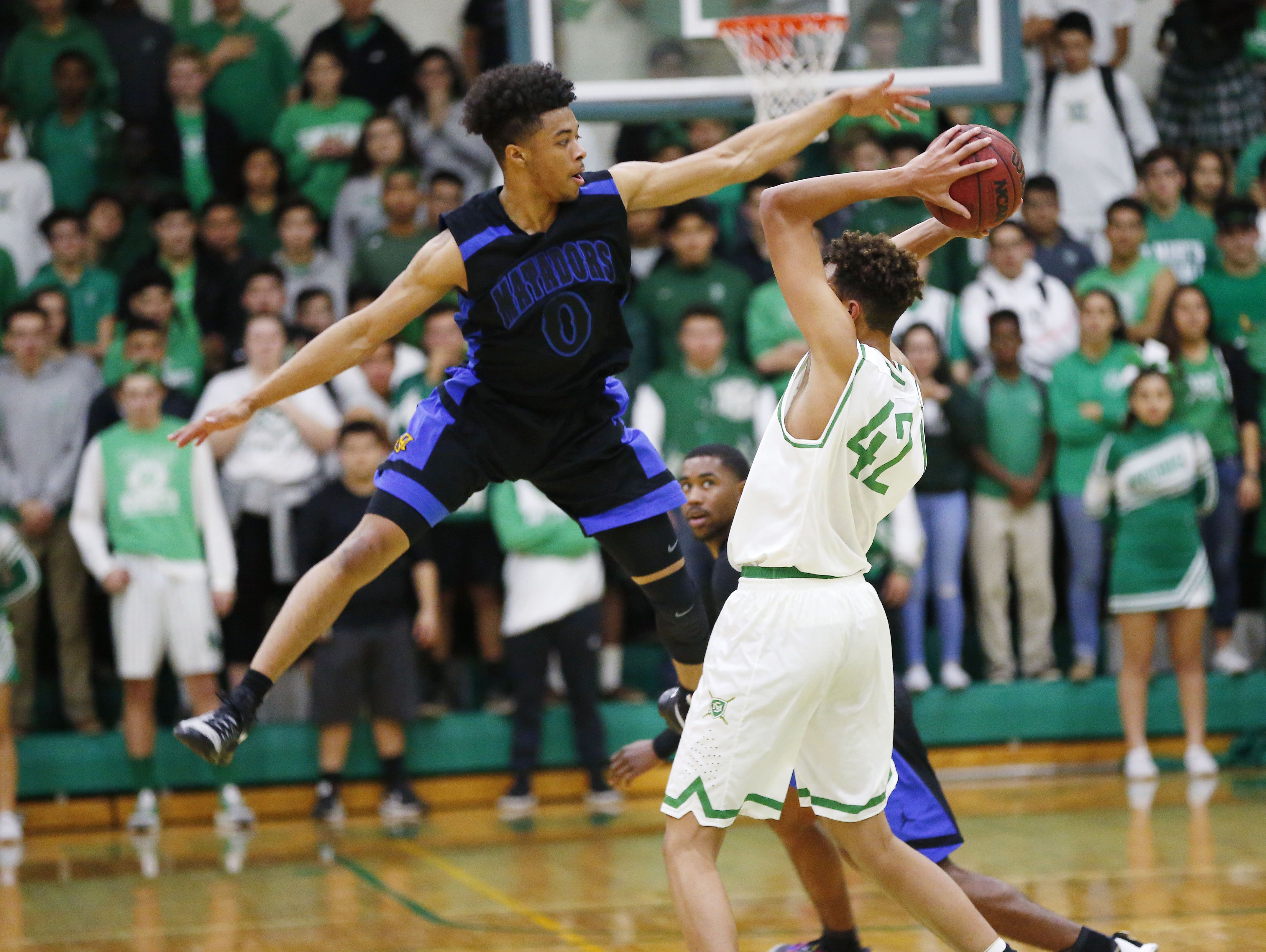 Shadow Mountain guard Marcus Shaver (0) defends against St. Mary's Kj Hymes (42) during the first half at the St. Mary's High School gym in Phoenix, Ariz., Jan. 24, 2017.