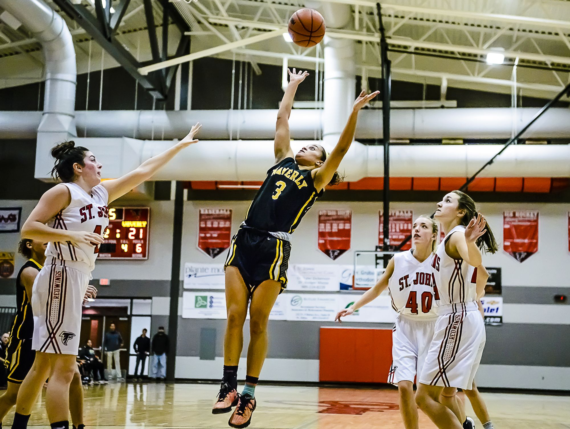 Jazlynn Wilcox ,center, of Waverly lays the ball up while surrounded by St. Johns defenders during their game Friday January 27, 2017 in St. Johns. KEVIN W. FOWLER PHOTO