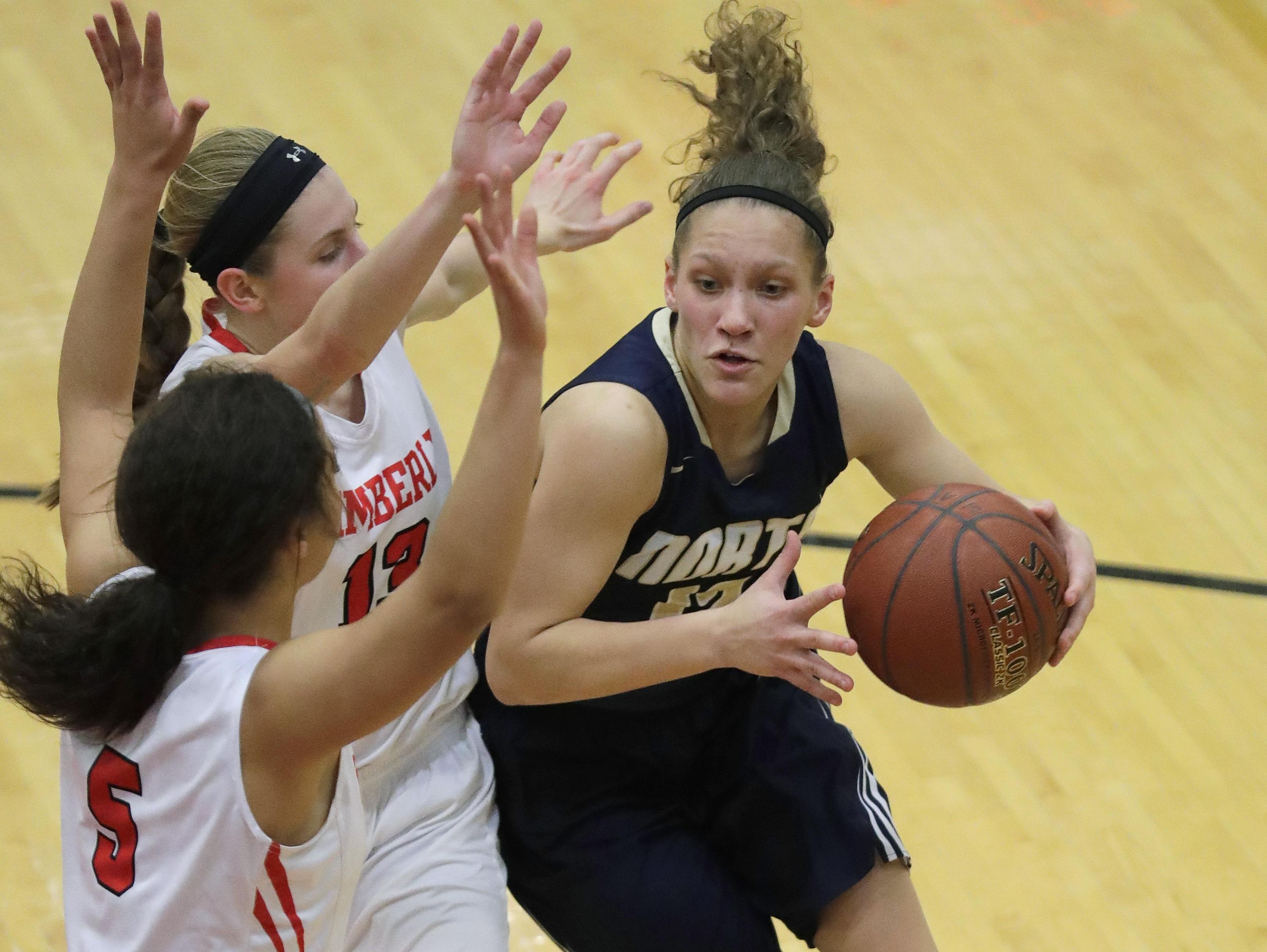 Appleton North's Callie Pohlman, right, drives to the hoop against Kimberly's Morgan Torzala (13) and Alina Hampton (5) during a Fox Valley Association game Tuesday in Kimberly.