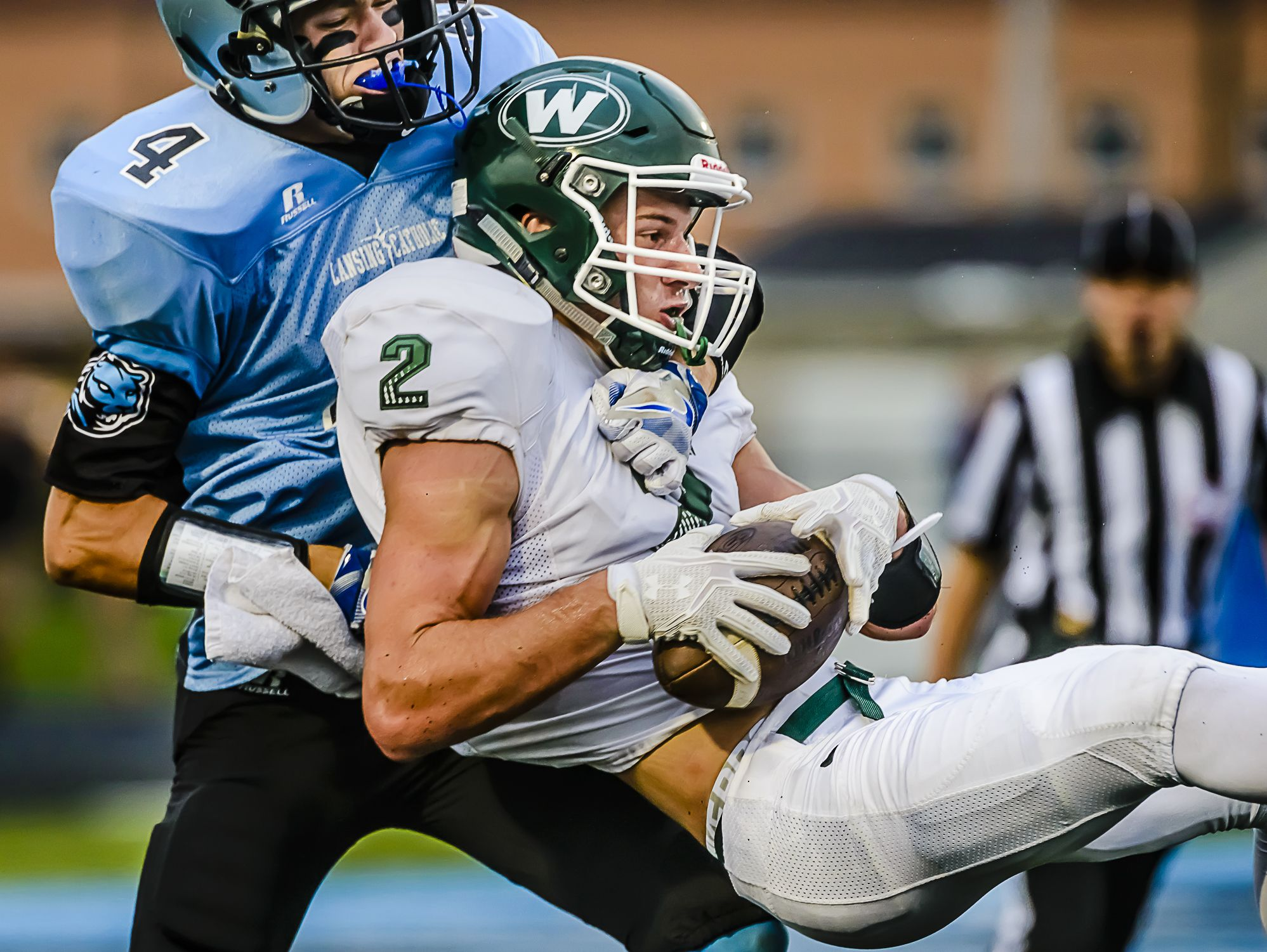 Sy Barnett, 2, of Williamston secures a pass despite the efforts of Konnor Maloney, 4, of Lansing Catholic at the Lansing Catholic 7 yard line late in the 1st quarter in 2015.