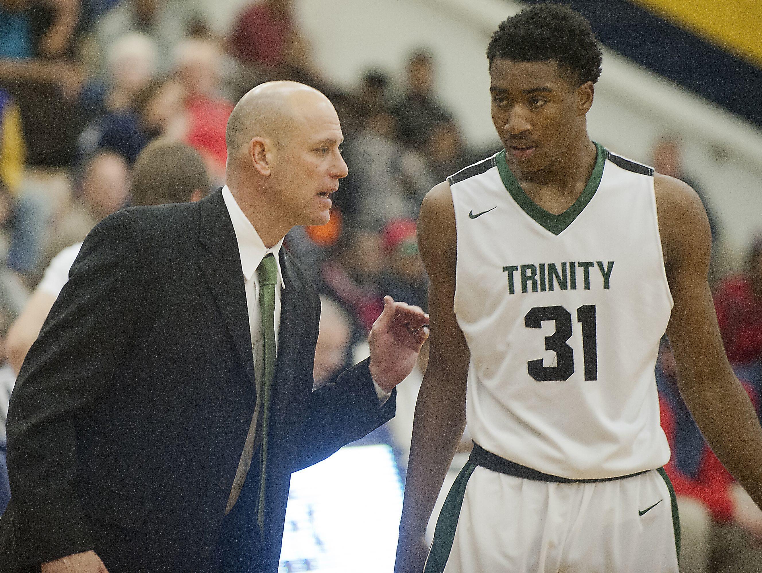 Trinity head basketball coach Mike Szabo talks to Trinity forward Jay Scrubb during a break in the action. 20 December 2016