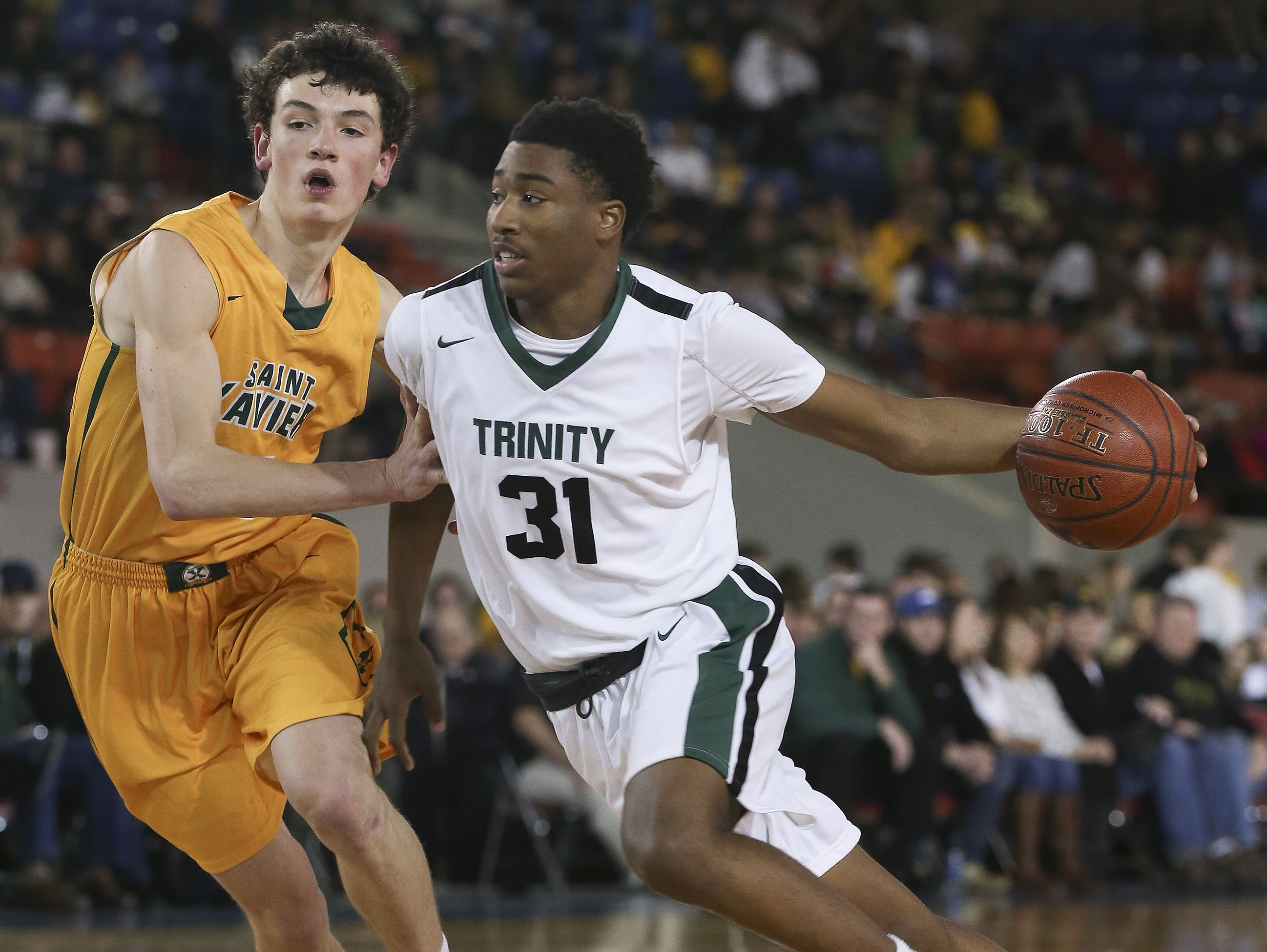 Trinity's Jay Scrubb (31) drives against St. X's Tyler Barnes (15) during their game at Broadbent Arena. Jan. 6, 2017