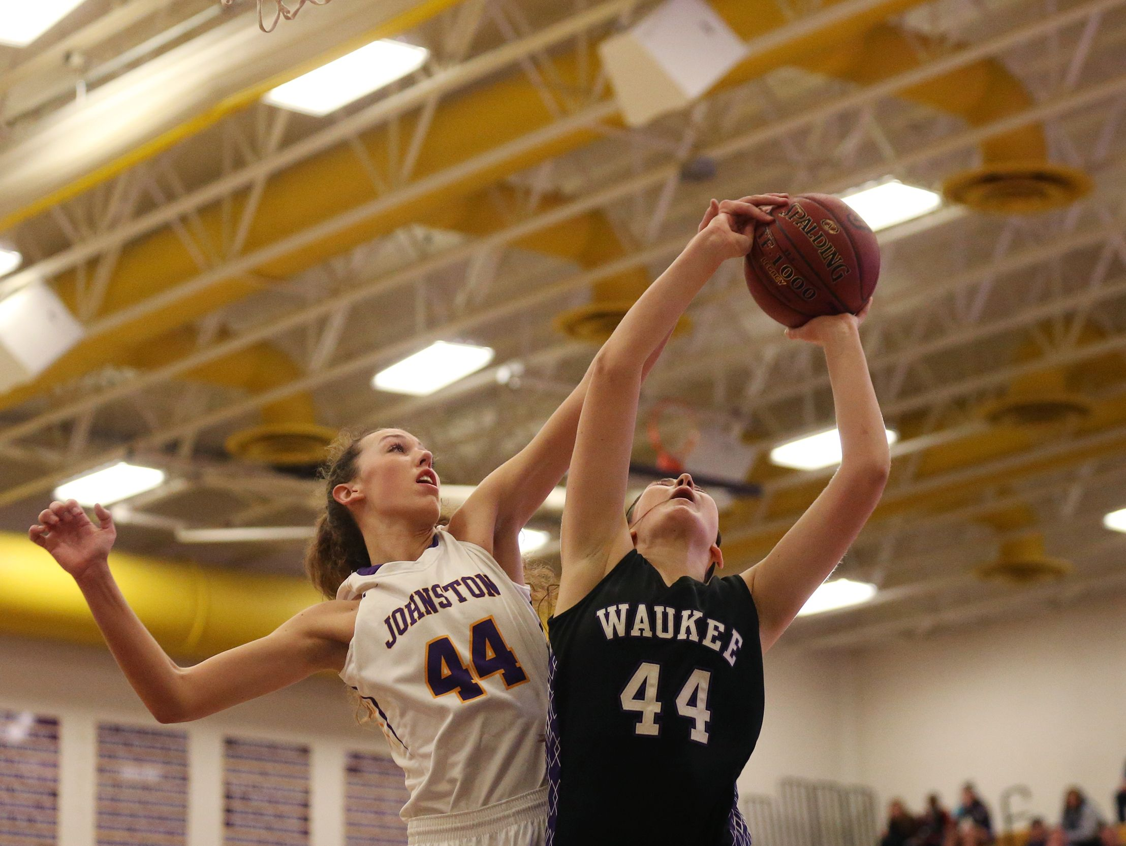 Johnston's Taryn Knuth tries to block a shot by Waukee's Paityn Rau during the Waukee at Johnston basketball game on Tuesday, Jan. 17 at Johnston High School. Waukee won in double overtime, 83-76.