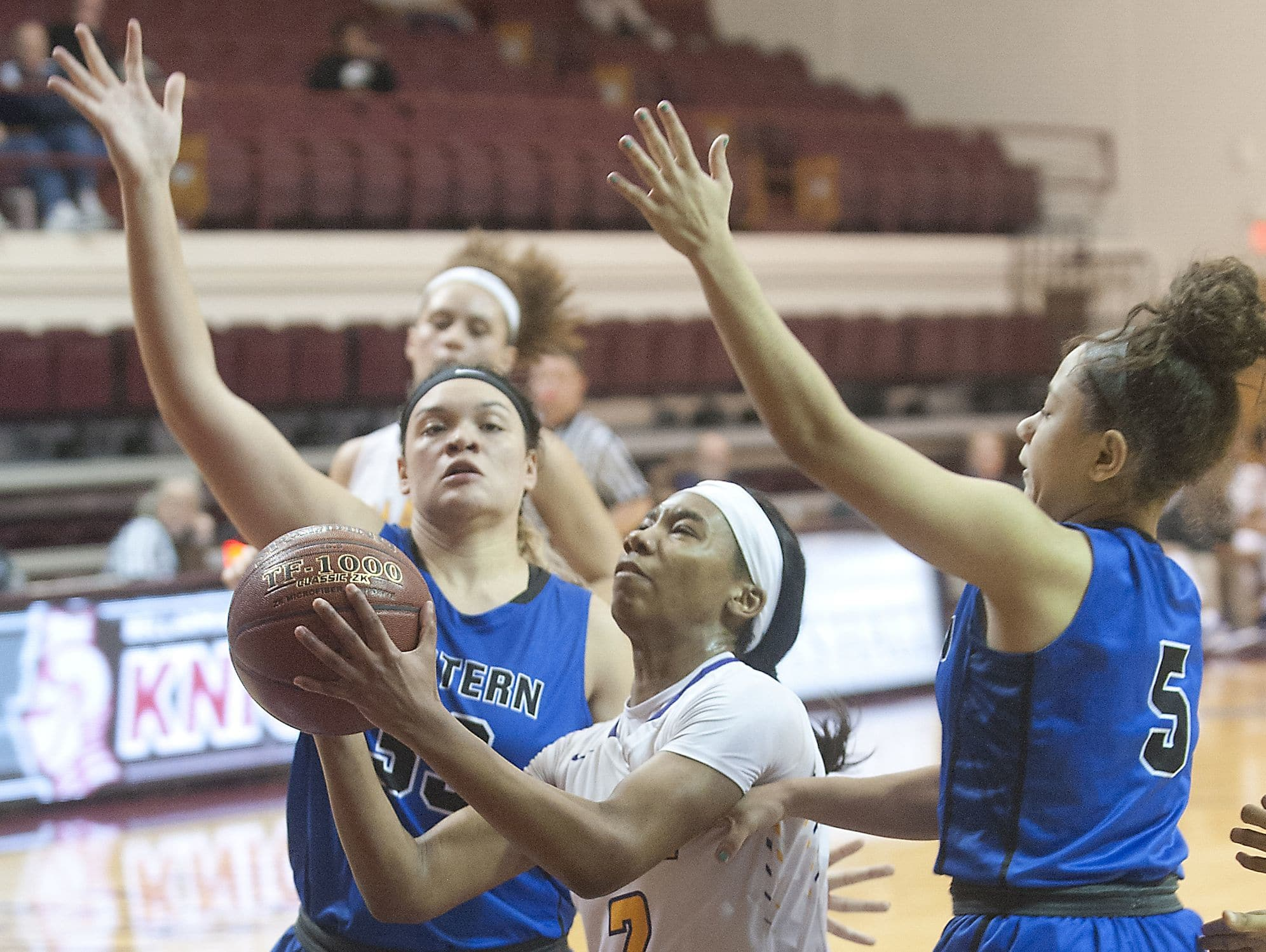 Male guard Ciaja Harbison drives between Eastern center Devin Beach,left, and Eastern guard Breanna Anthony, right, in the second round of the Girls LIT. 25 January 2017