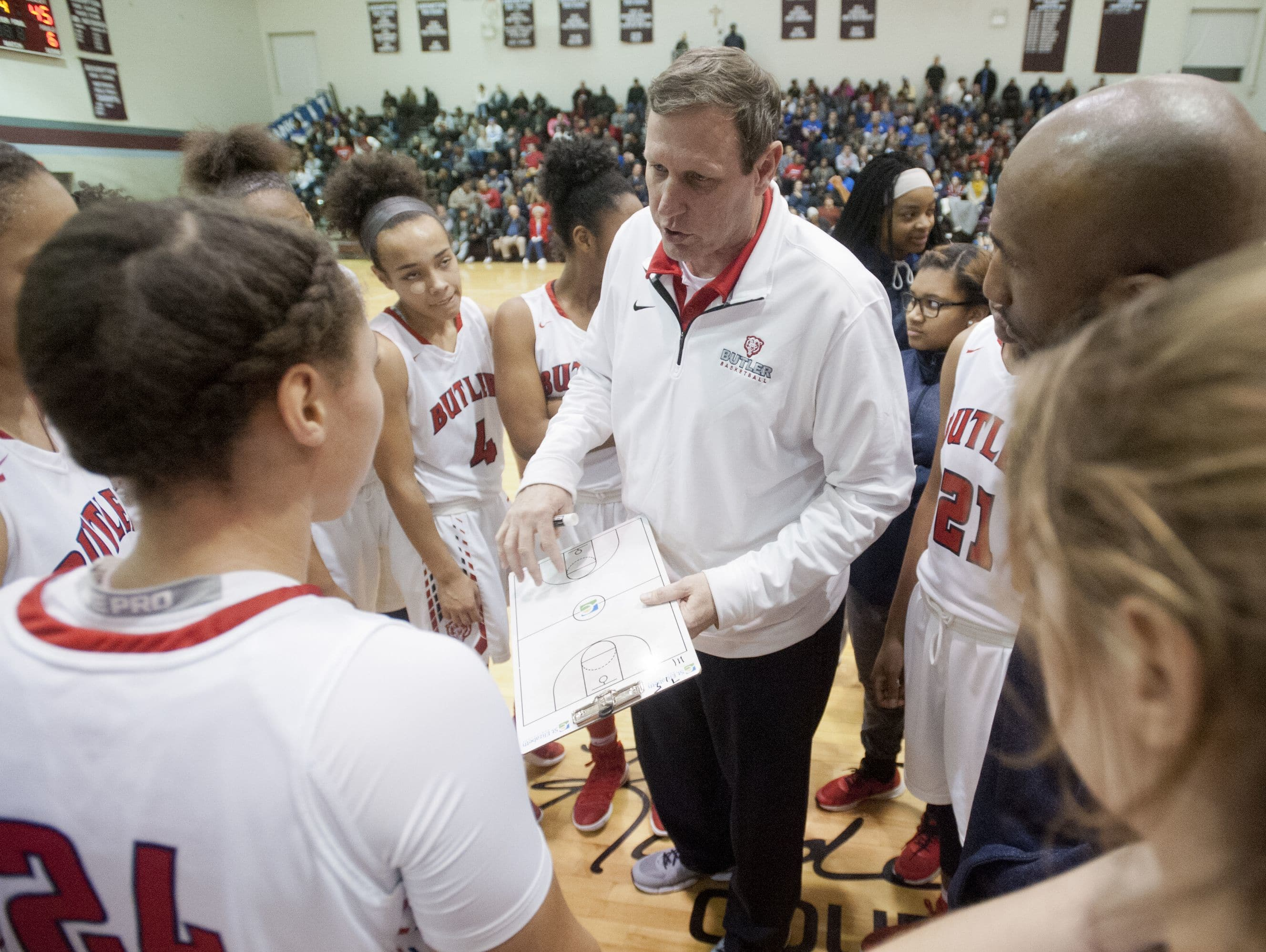 Butler head basketball coach Larry Just charts a play during a time-out in the Girls' LIT championship. 28 January 2017