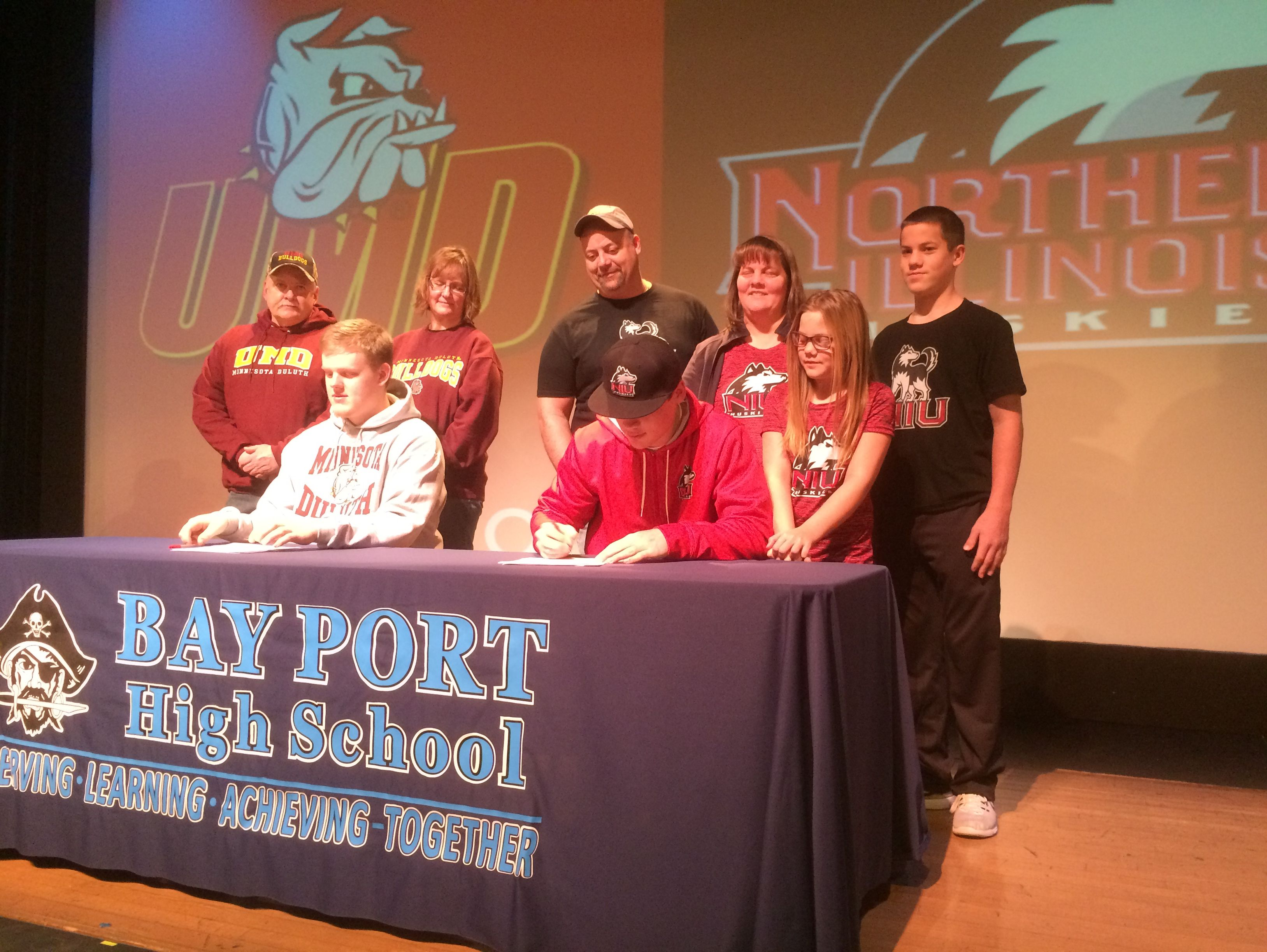 Bay Port seniors Matt Lorbeck (right) and Jake Hansen (left) sign national letters of intent on Wednesday with college football programs. Lorbeck signed with Northern Illinois University, while Hansen signed with Minnesota-Duluth.